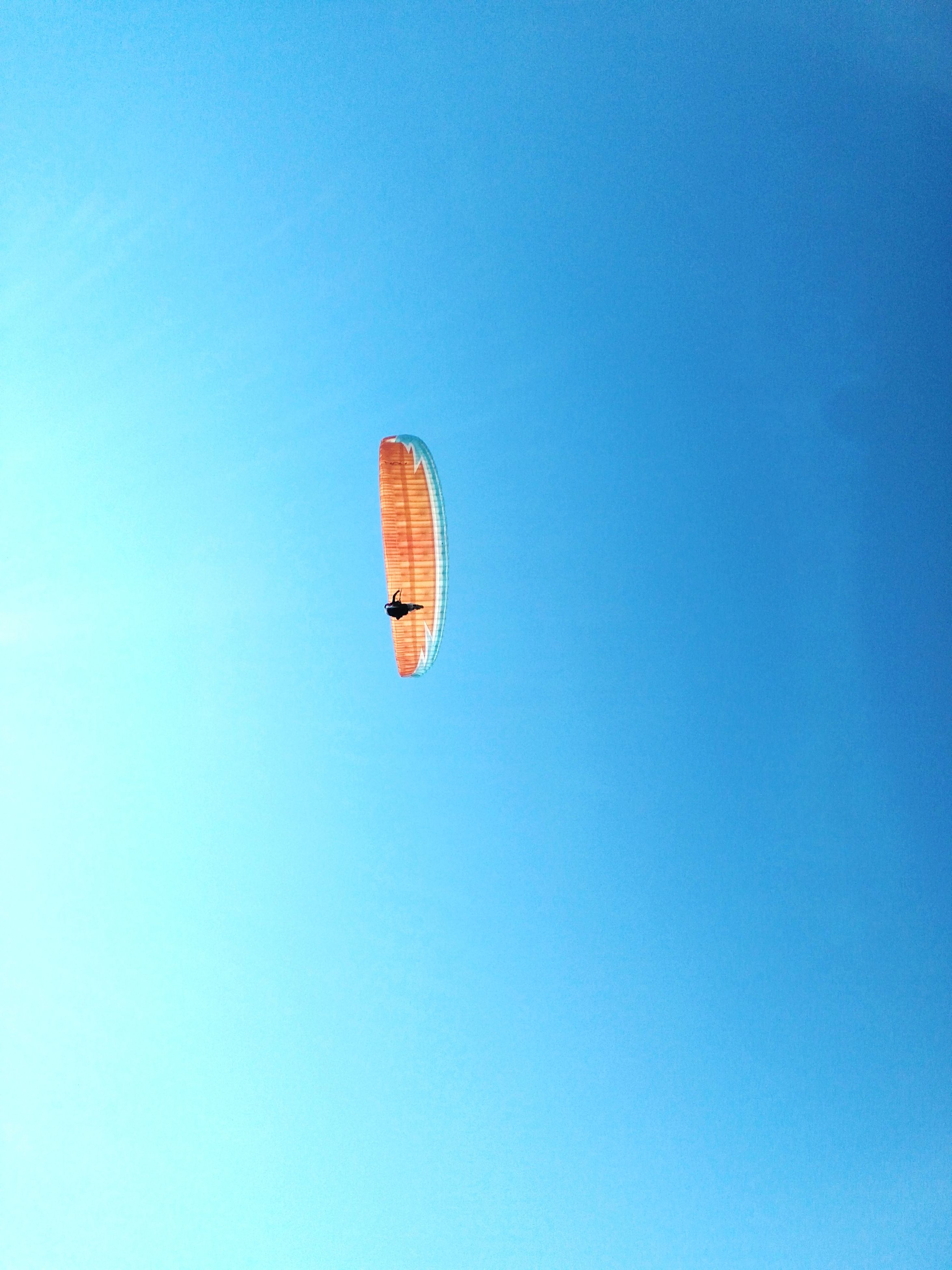 adventure, parachute, extreme sports, low angle view, mid-air, blue, sport, flying, leisure activity, clear sky, paragliding, outdoors, day, nature, real people, one person, sky, people