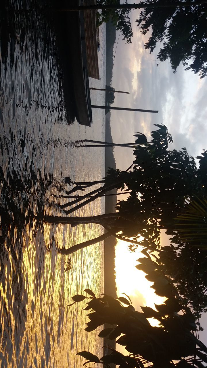 water, reflection, nature, tree, silhouette, outdoors, sunset, beauty in nature, scenics, sky, cloud - sky, sunlight, tranquil scene, lake, tranquility, no people, built structure, architecture, plant, day, building exterior, grass