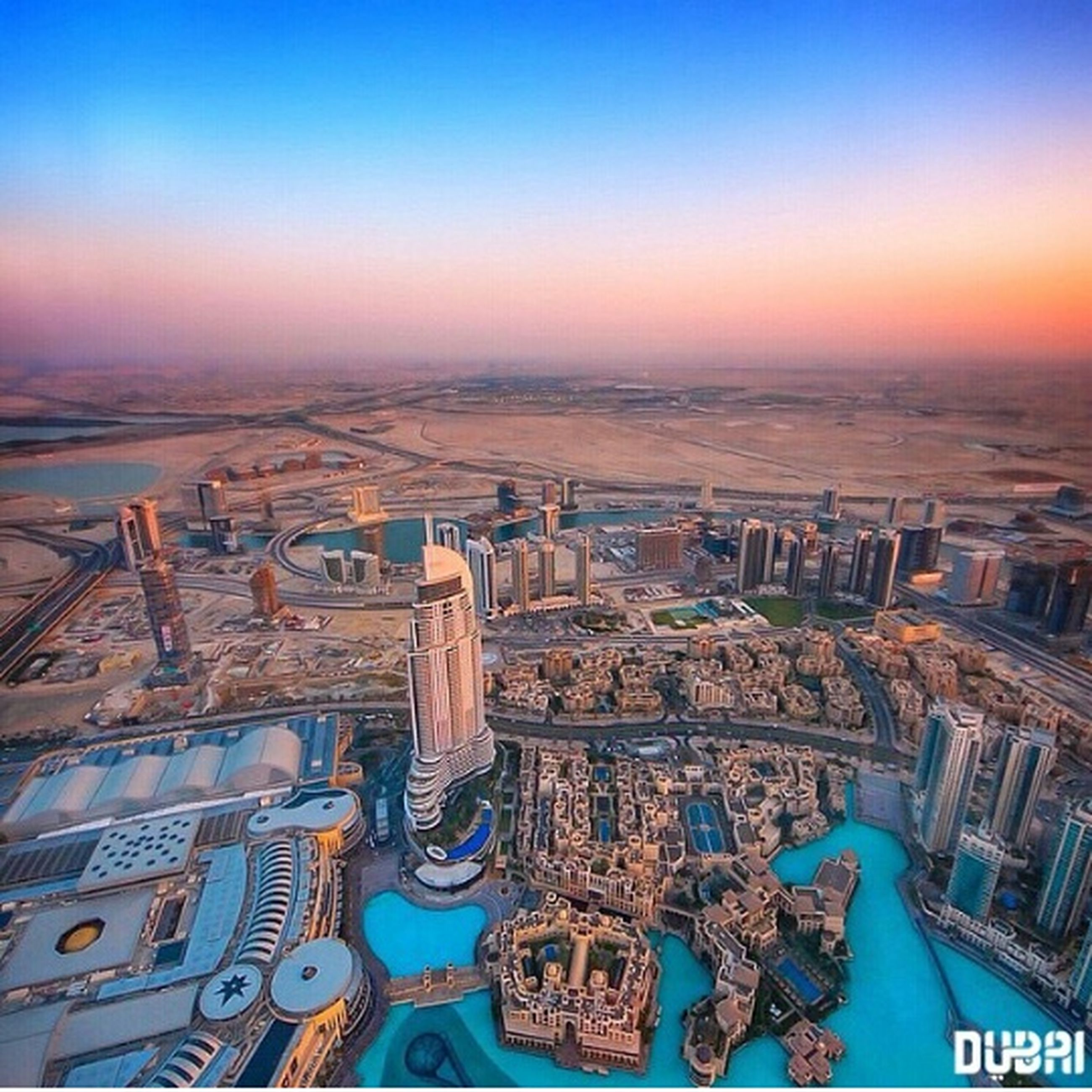 cityscape, city, architecture, built structure, building exterior, sunset, blue, high angle view, crowded, sea, sky, water, skyscraper, clear sky, horizon over water, travel destinations, no people, outdoors, aerial view, residential district