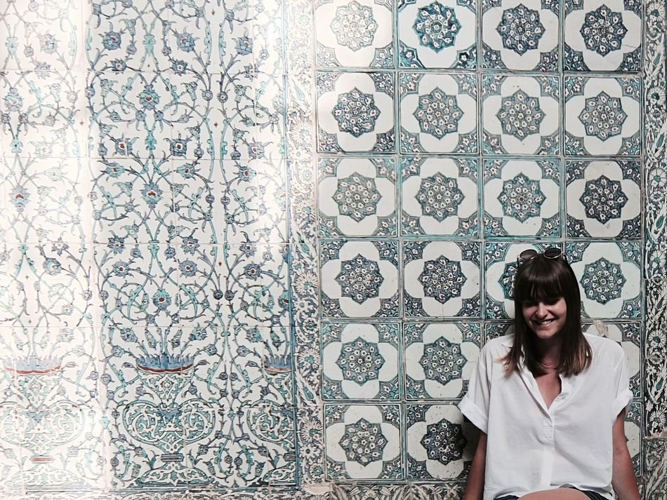 Me in Topkapi Palace in Istanbul. The Tiled Walls are everywhere and they are just gorgeous! Woman Woman Portrait Wall Girl Traveling Faded White Shirt Casual Clothing Smiling Tiles Smile Self Portrait Selfportrait Everyday Emotion Portrait Of A Woman Istanbul Istanbul Turkey Topkapi Palace Topkapi Leaning Sitting Oriental Oriental Design Orient Blue Background