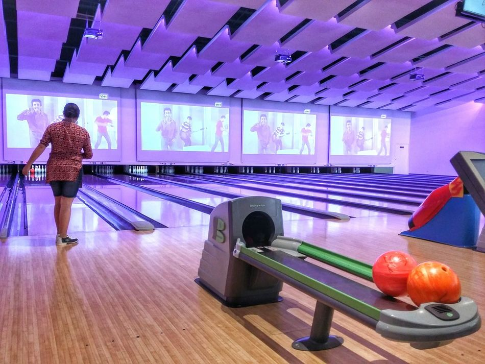 Making a strike in bowling. Indoors  One Person Bowling Bowling Balls Bowling Alley Bowling Time Purple Strike Bowling Pins Screens Bowlingshoes Fun Purple Light Colorful Funny Game