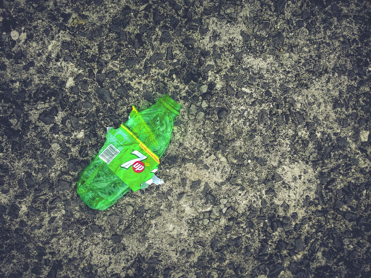 Top view of crushed 7up plastic bottle on concrete floor 7up Concrete Floor Copy Space Crushed Day Environmental Issues Green Color Horizontal No People Outdoors Plastic Bottle Recyclable Recycle Top View Waste