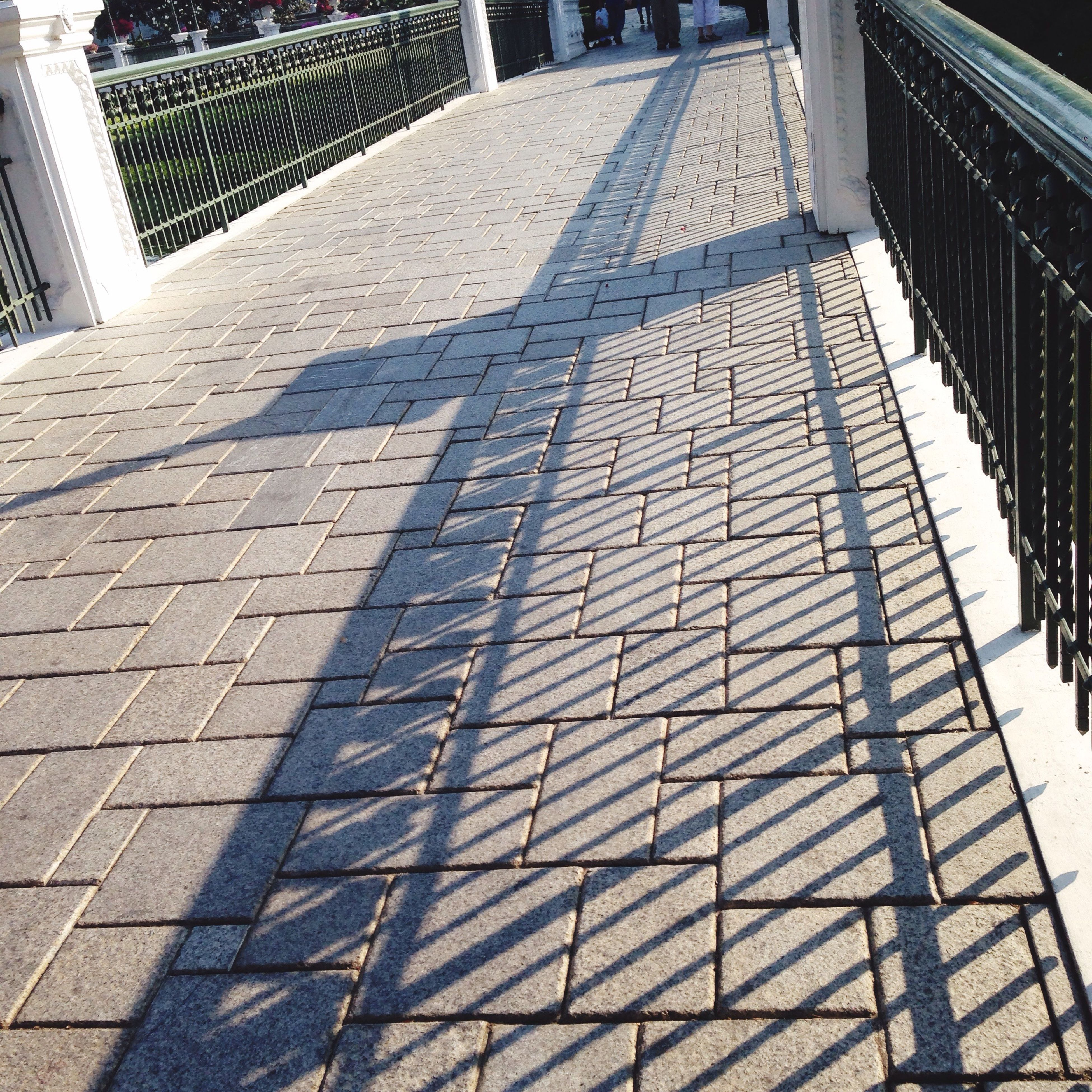 architecture, built structure, pattern, the way forward, diminishing perspective, shadow, sunlight, building exterior, walkway, cobblestone, footpath, paving stone, day, in a row, tiled floor, vanishing point, no people, outdoors, city, empty