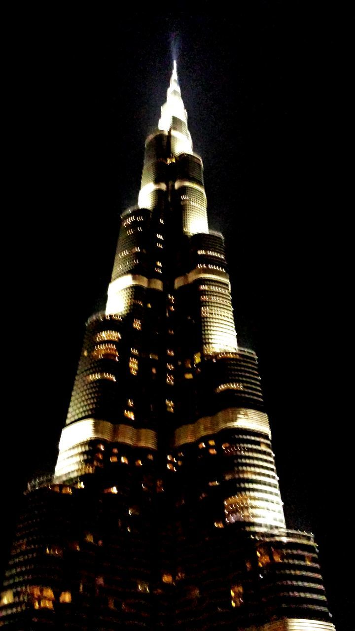 night, architecture, tall - high, building exterior, built structure, low angle view, travel destinations, tourism, skyscraper, black background, travel, no people, illuminated, gold colored, place of worship, modern, statue, clear sky, outdoors, ancient civilization, sky
