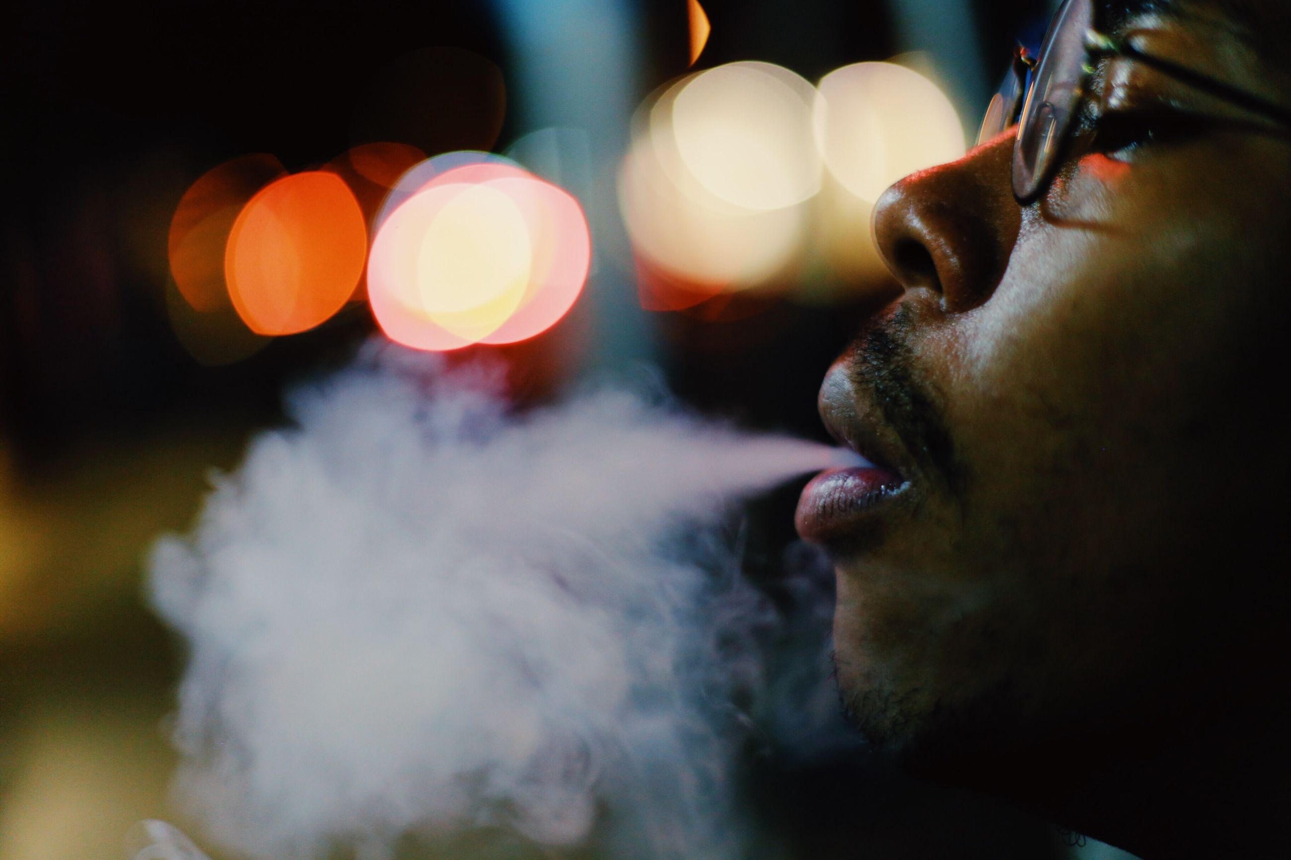 night, one person, smoke - physical structure, real people, close-up, side view, indoors, men, beard, bad habit, illuminated, people