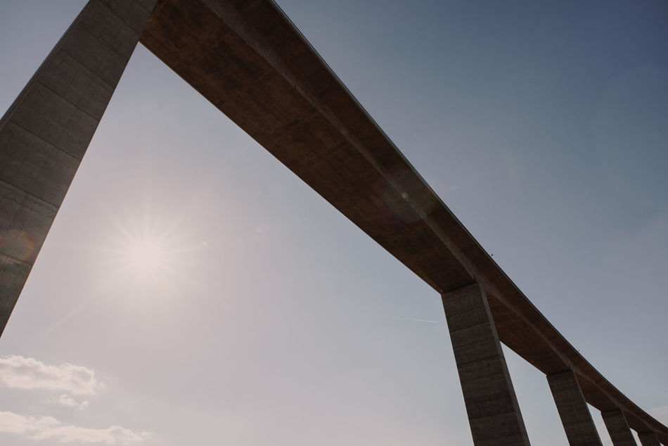 Connected Architecture Bridge - Man Made Structure Built Structure Connection Day Highway Lens Flare Low Angle View Minimal Outdoors Sky Wide Angle