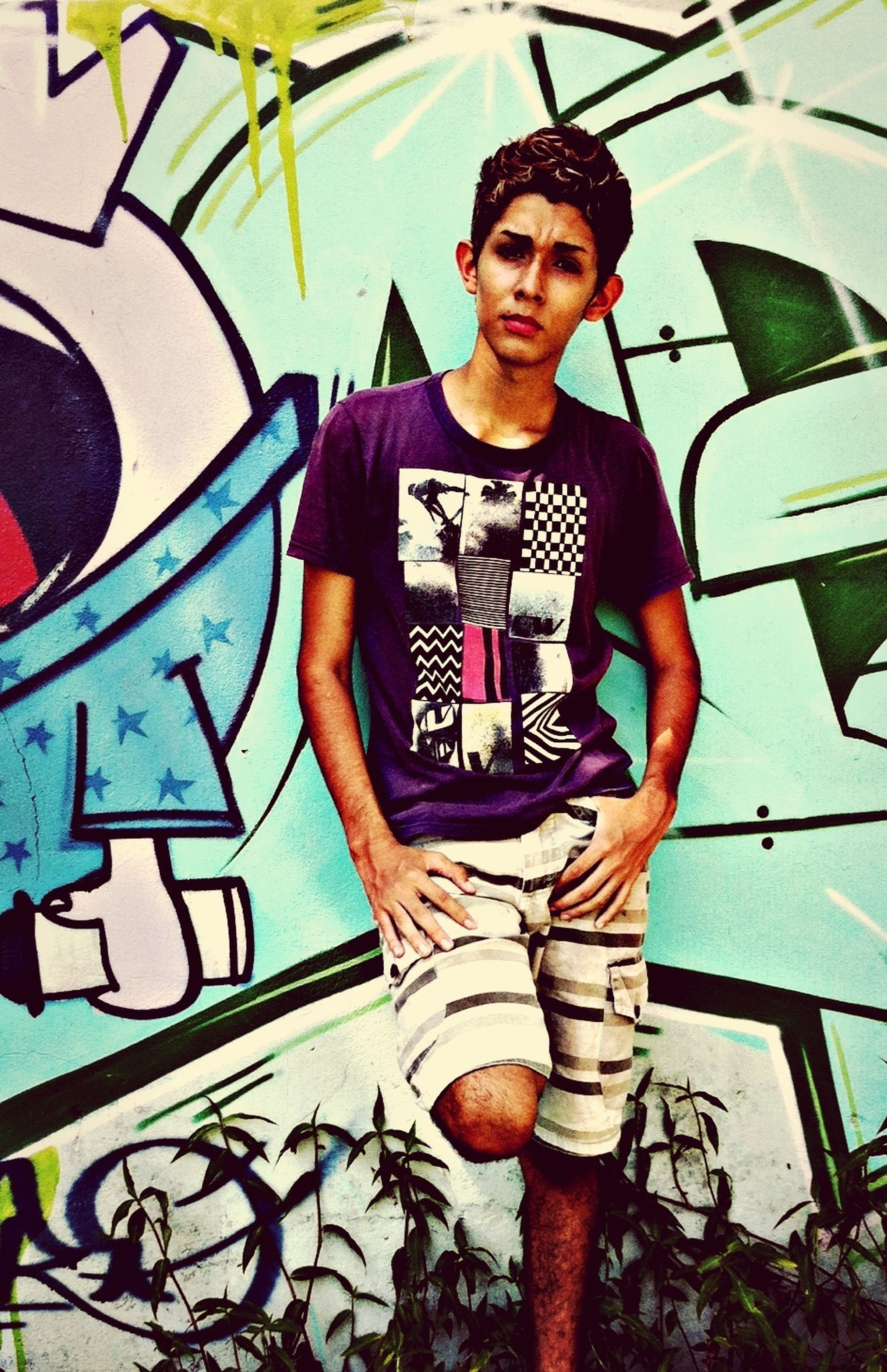 young adult, lifestyles, person, looking at camera, leisure activity, portrait, casual clothing, young women, smiling, front view, happiness, graffiti, three quarter length, standing, wall - building feature, enjoyment