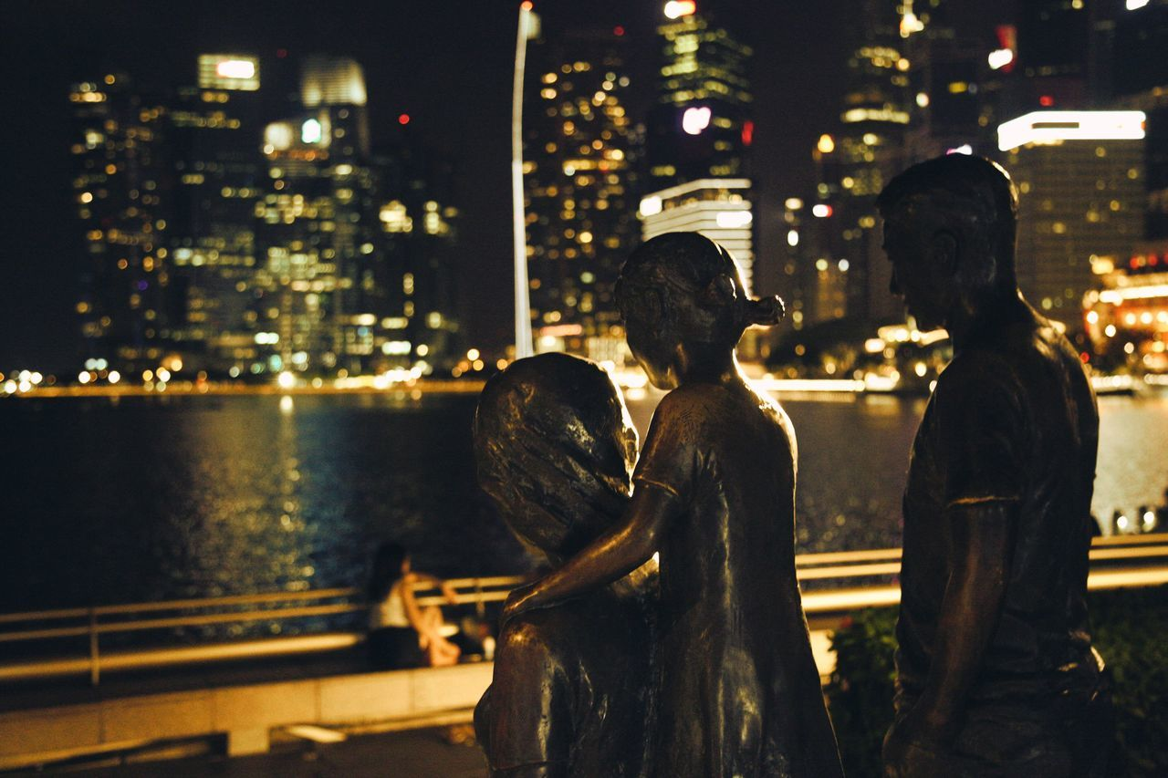 building exterior, architecture, city, built structure, night, illuminated, two people, skyscraper, outdoors, real people, cityscape, statue, men, togetherness, people