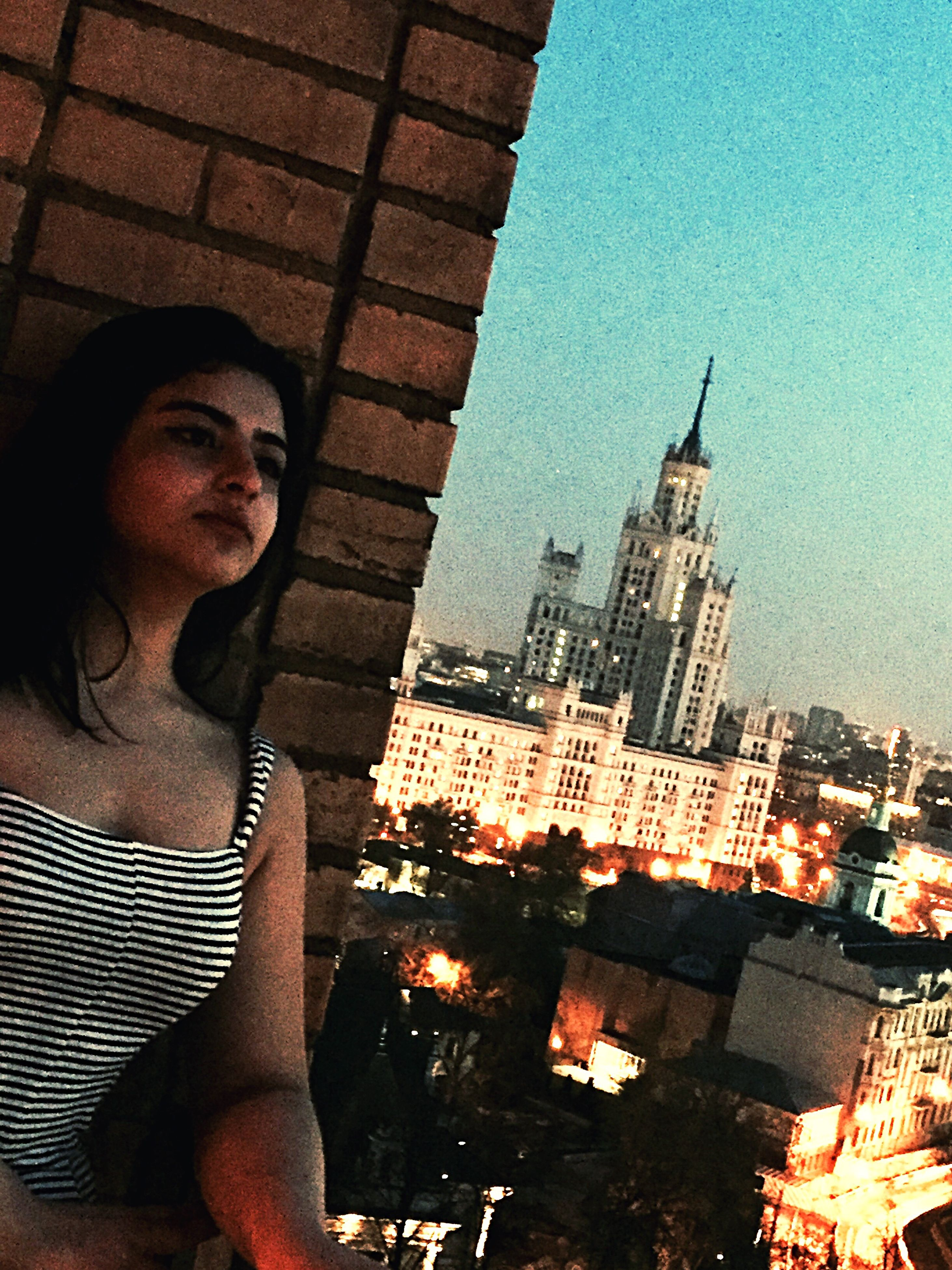 architecture, building exterior, built structure, real people, one person, outdoors, night, standing, lifestyles, low angle view, young adult, leisure activity, city, illuminated, clear sky, cityscape, sky, young women, people