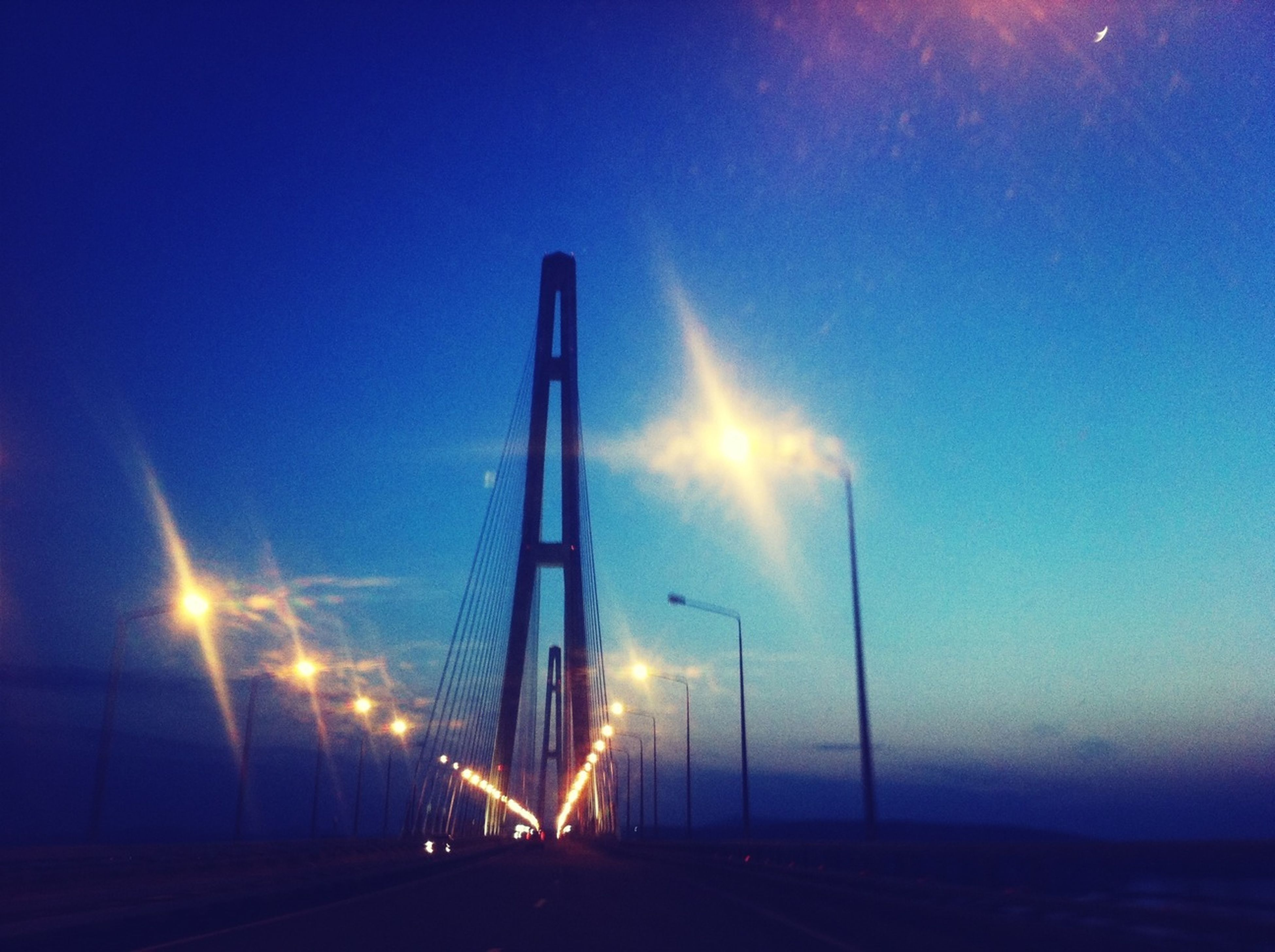 transportation, sky, connection, illuminated, road, blue, sunset, the way forward, suspension bridge, dusk, engineering, bridge - man made structure, built structure, street light, night, outdoors, nature, no people, lens flare, mode of transport