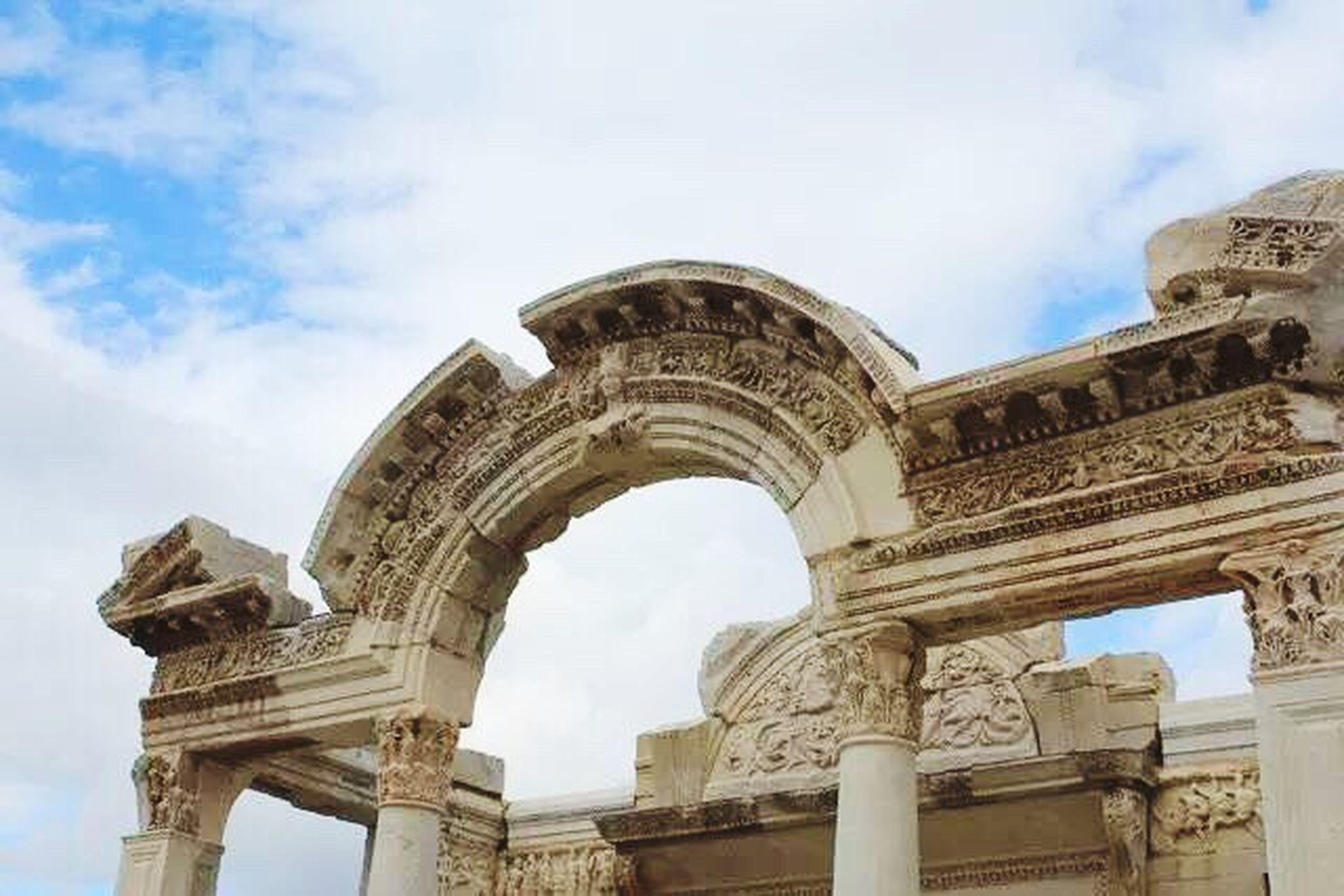 architecture, sky, arch, cloud - sky, travel destinations, city, outdoors, building exterior, built structure, history, triumphal arch, low angle view, day, cultures, no people, ancient civilization