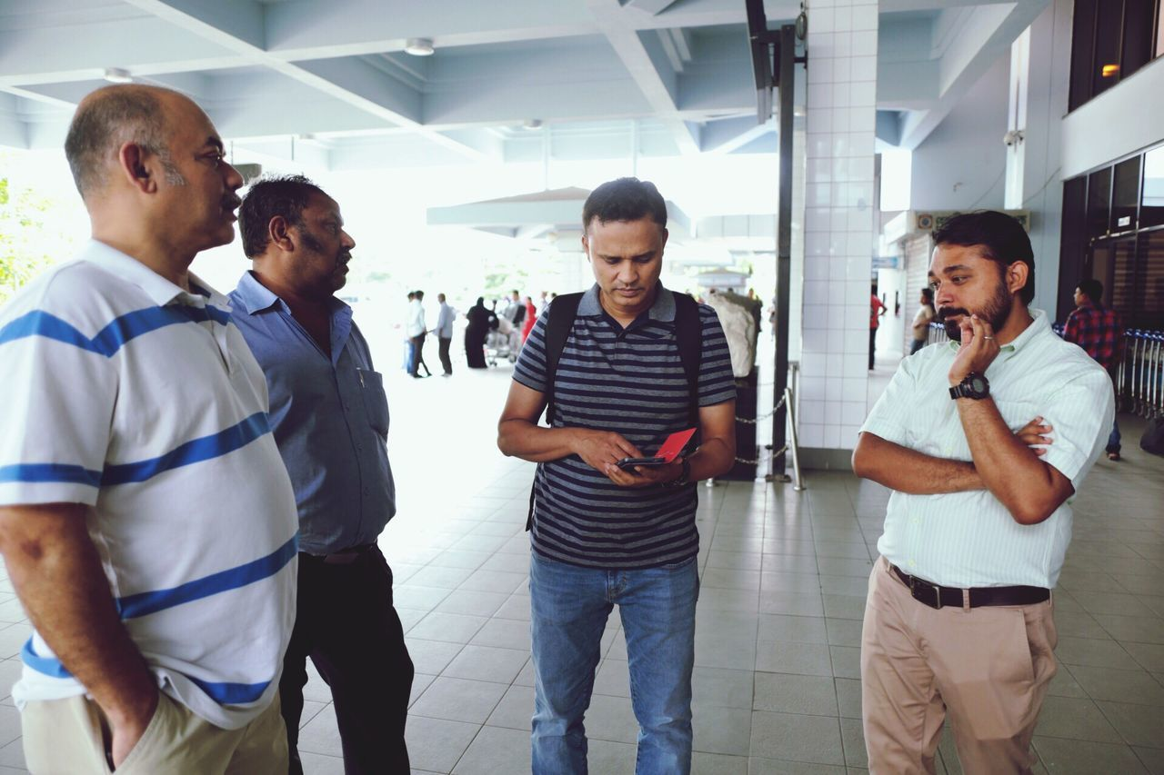 communication, standing, mobile phone, wireless technology, using phone, casual clothing, young men, indoors, real people, technology, walking, young adult, men, lifestyles, day, young women, architecture, adult, people