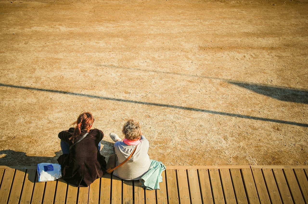 High Angle View Of Friends Sitting On Boardwalk Against Field During Sunny Day