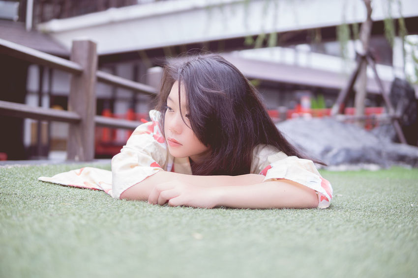 Beautiful Woman Black Hair Casual Clothing Childhood Close-up Day Girls Grass Headshot Leisure Activity Lifestyles Lying Down One Person Outdoors People Real People Relaxation Selective Focus Young Adult Young Women