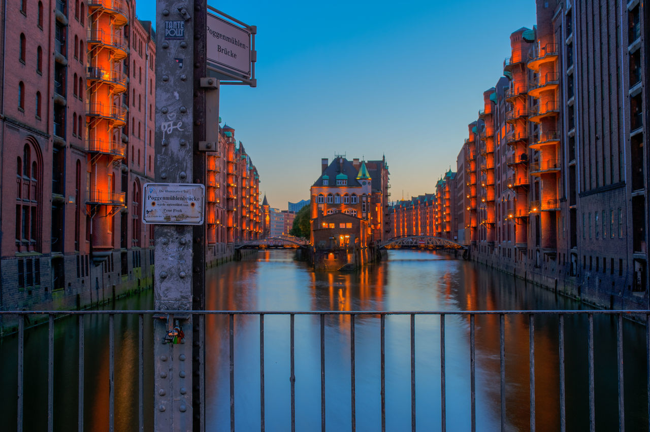 architecture, built structure, building exterior, water, river, sky, sunset, waterfront, outdoors, reflection, bridge - man made structure, transportation, no people, city, travel destinations, nature, illuminated, day