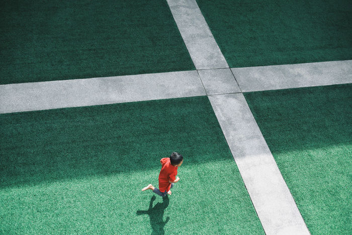 Cross EyeEm Ready   Green Artificial Grass Boy Running Courtyard  Grass Green Color High Angle View Lifestyles Playing Red Red Shirt Sports Track Fresh On Market 2018