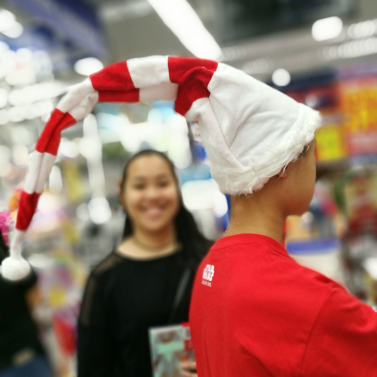red, rear view, two people, focus on foreground, real people, women, smiling, happiness, indoors, food, young women, day, young adult, close-up, supermarket, people