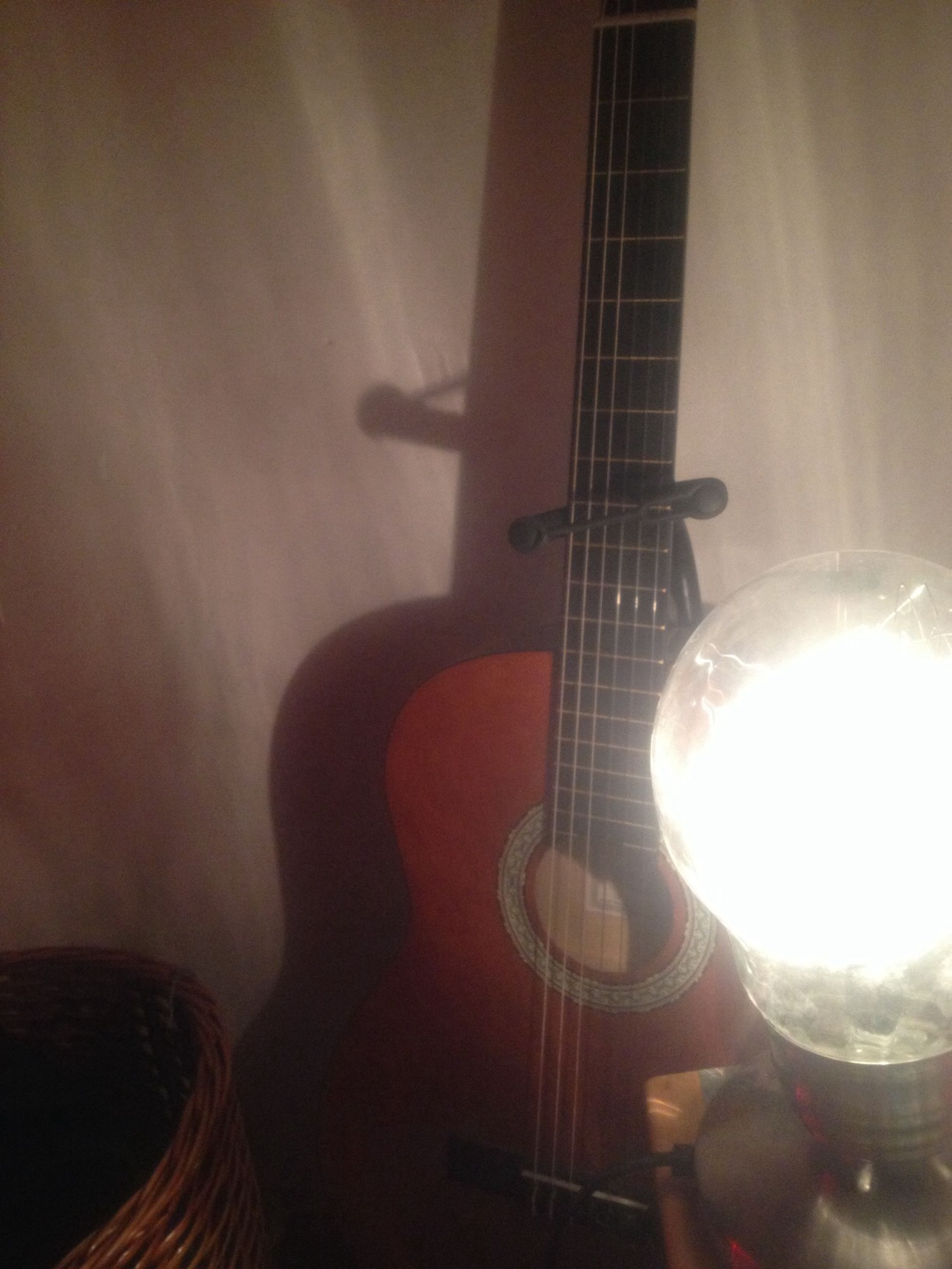 indoors, music, musical instrument, guitar, illuminated, arts culture and entertainment, lighting equipment, musical equipment, musical instrument string, home interior, electricity, close-up, light - natural phenomenon, technology, glowing, night, string instrument, focus on foreground, no people, low angle view