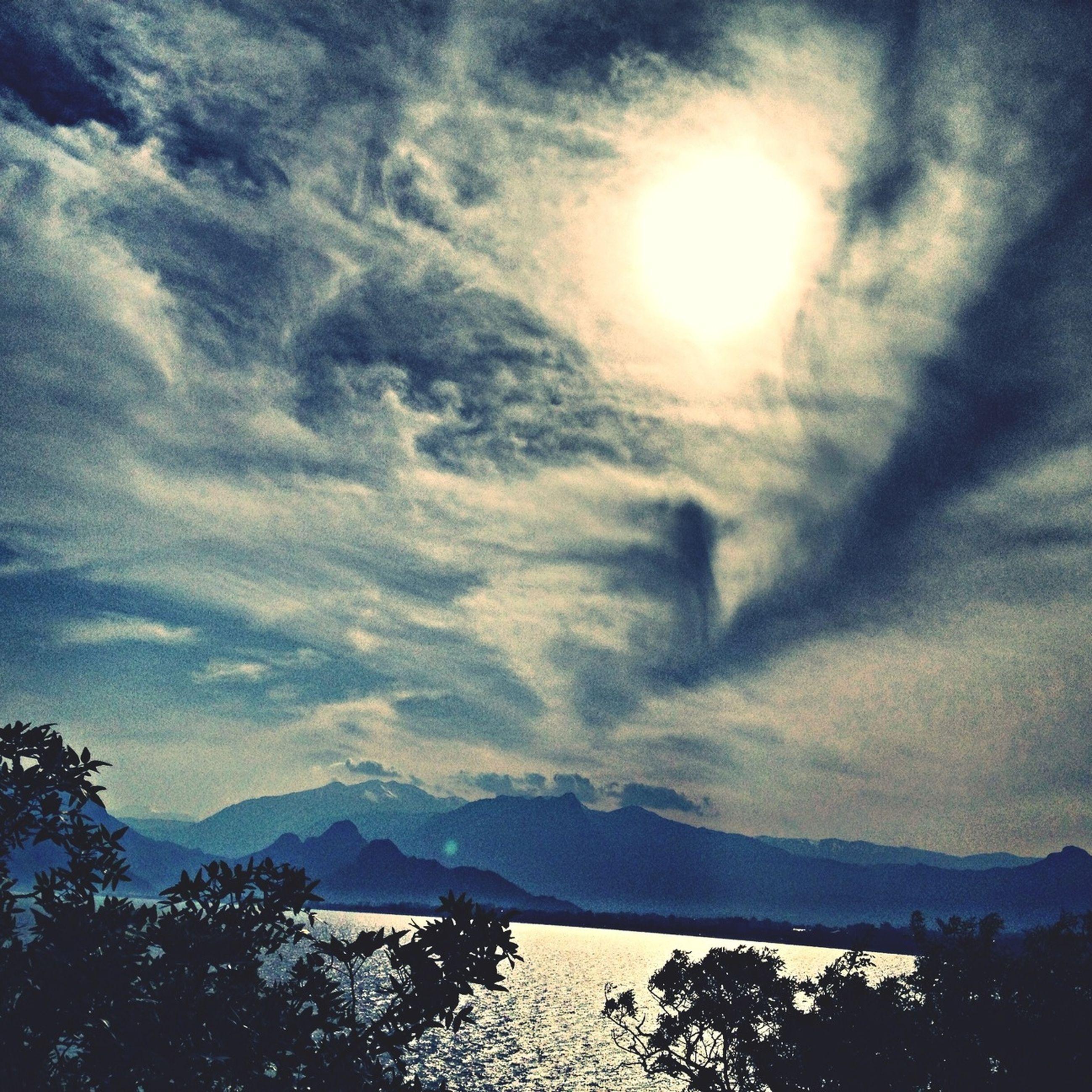 mountain, tranquil scene, scenics, tranquility, beauty in nature, sky, mountain range, cloud - sky, nature, sun, tree, idyllic, weather, silhouette, cloudy, landscape, sunlight, non-urban scene, sunbeam, cloud