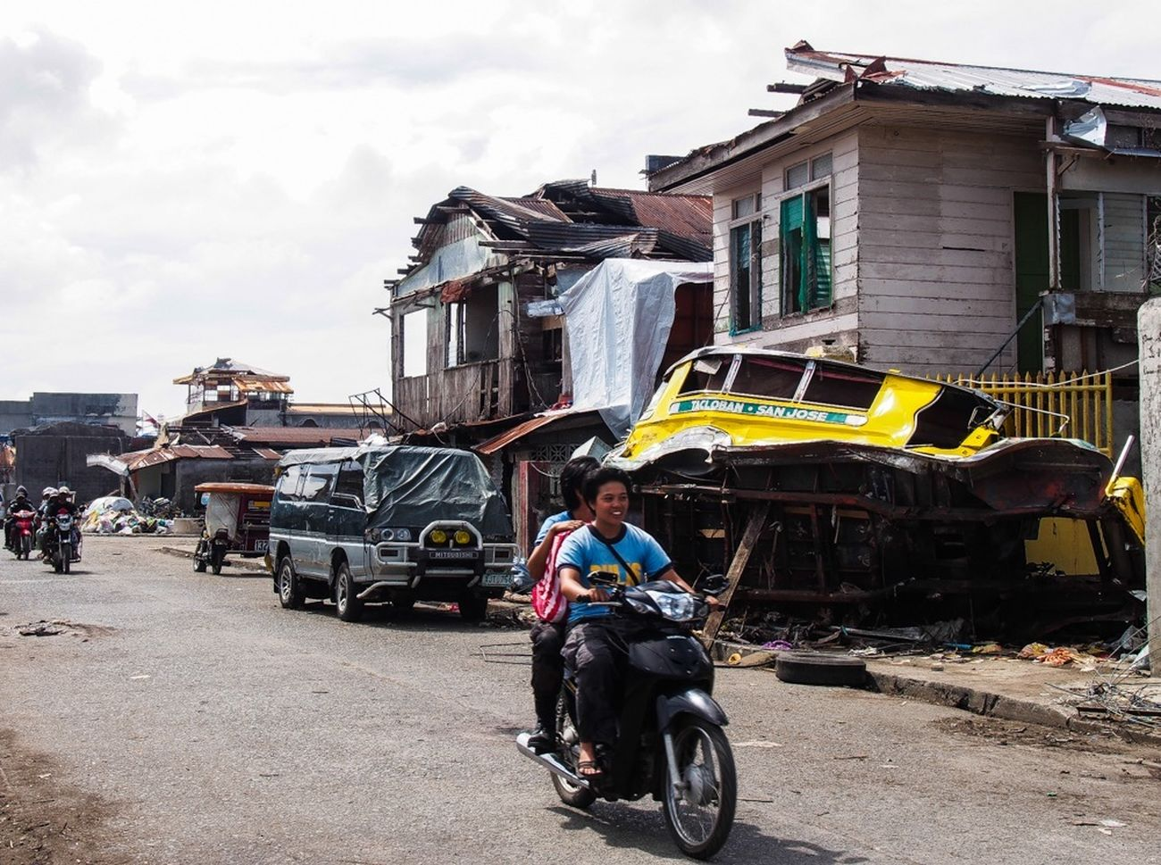 Police officers riding through the devastated streets of Tacloban, more than one month after Typhoon Haiyan . EyeEmbestshots Streetphotography Documentary