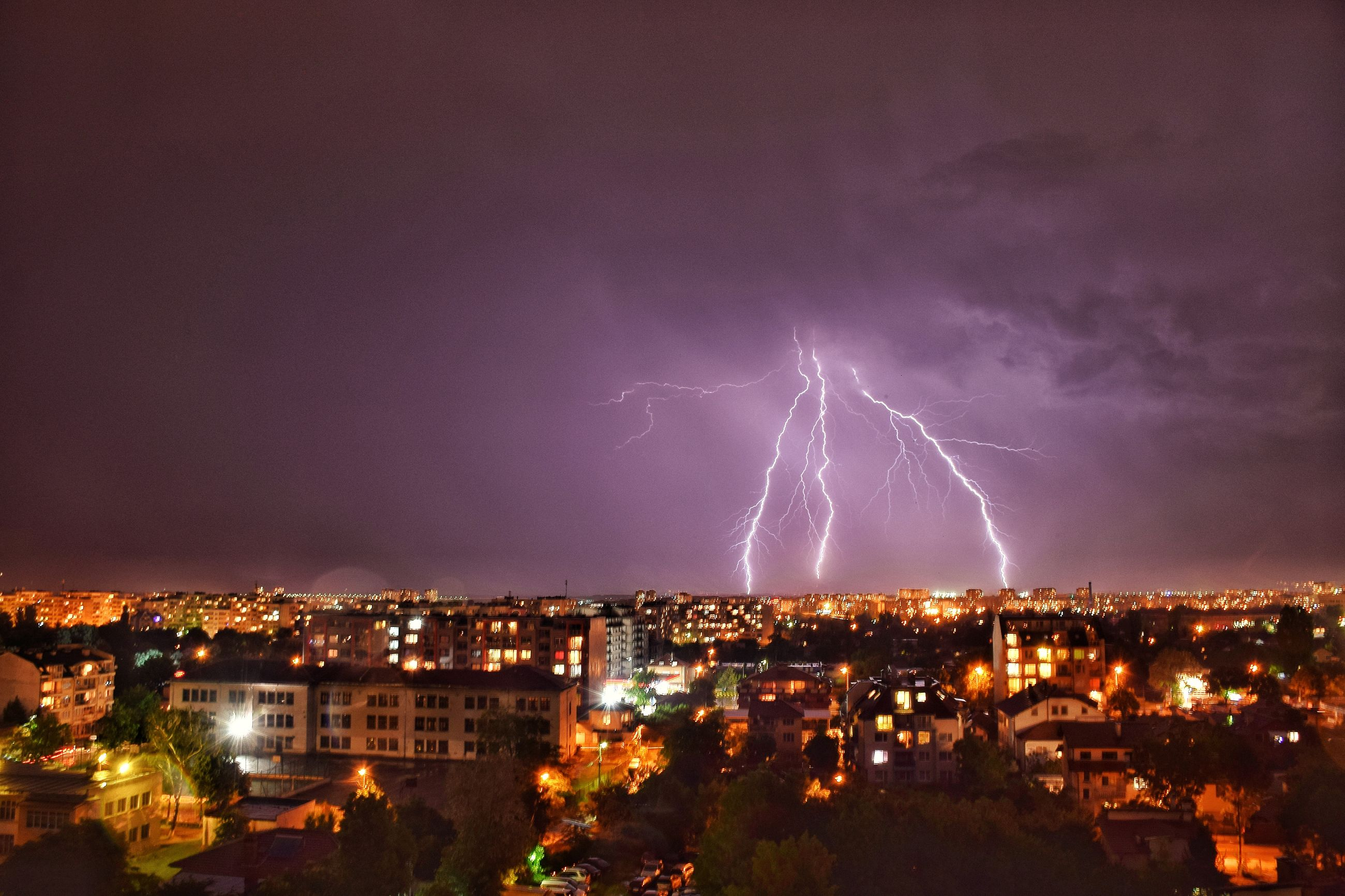 architecture, building exterior, built structure, cityscape, lightning, illuminated, night, city, sky, thunderstorm, no people, forked lightning, outdoors, residential building, power in nature, storm cloud, nature