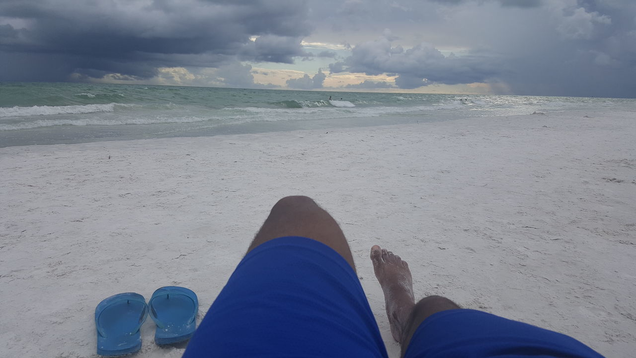 human leg, low section, personal perspective, beach, one person, human body part, shoe, sea, sand, real people, human foot, cloud - sky, day, outdoors, water, sky, nature, horizon over water, leisure activity, blue, beauty in nature, people