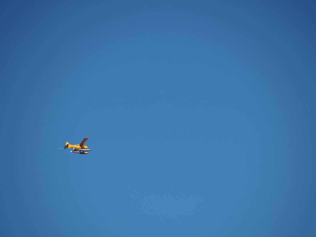 A yellow hydroplane in the air Air Air Vehicle Aircraft Aircraft In The Sky Airplane Blue Blue Sky Clear Sky Fly Flying Flying High Hydroplane In The Air Low Angle View Mid-air Minimal Minimalism Negative Space Noedit On The Move Plane Sky Transportation Yellow Yellow Plane