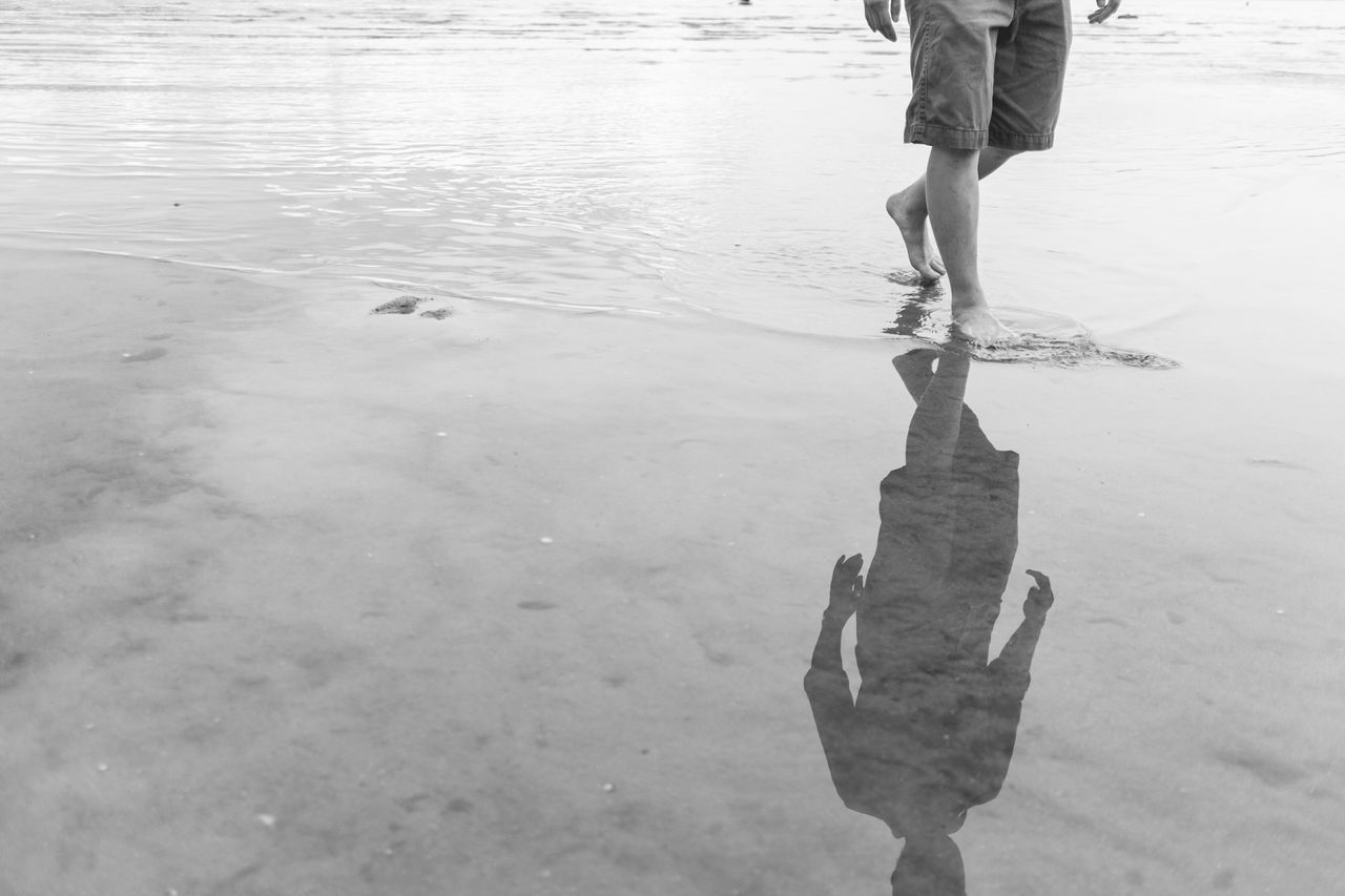 Low Section Of Man With Reflection On Shore