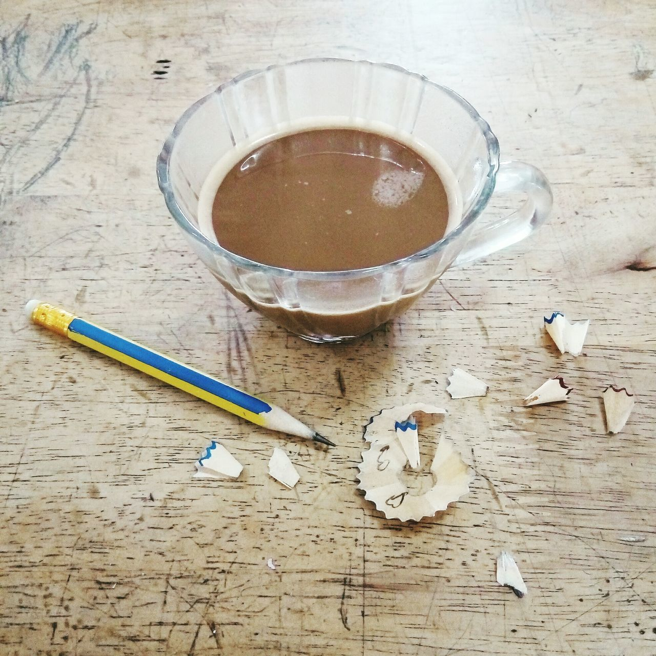 High Angle View Of Pencil By Tea Cup On Wooden Table