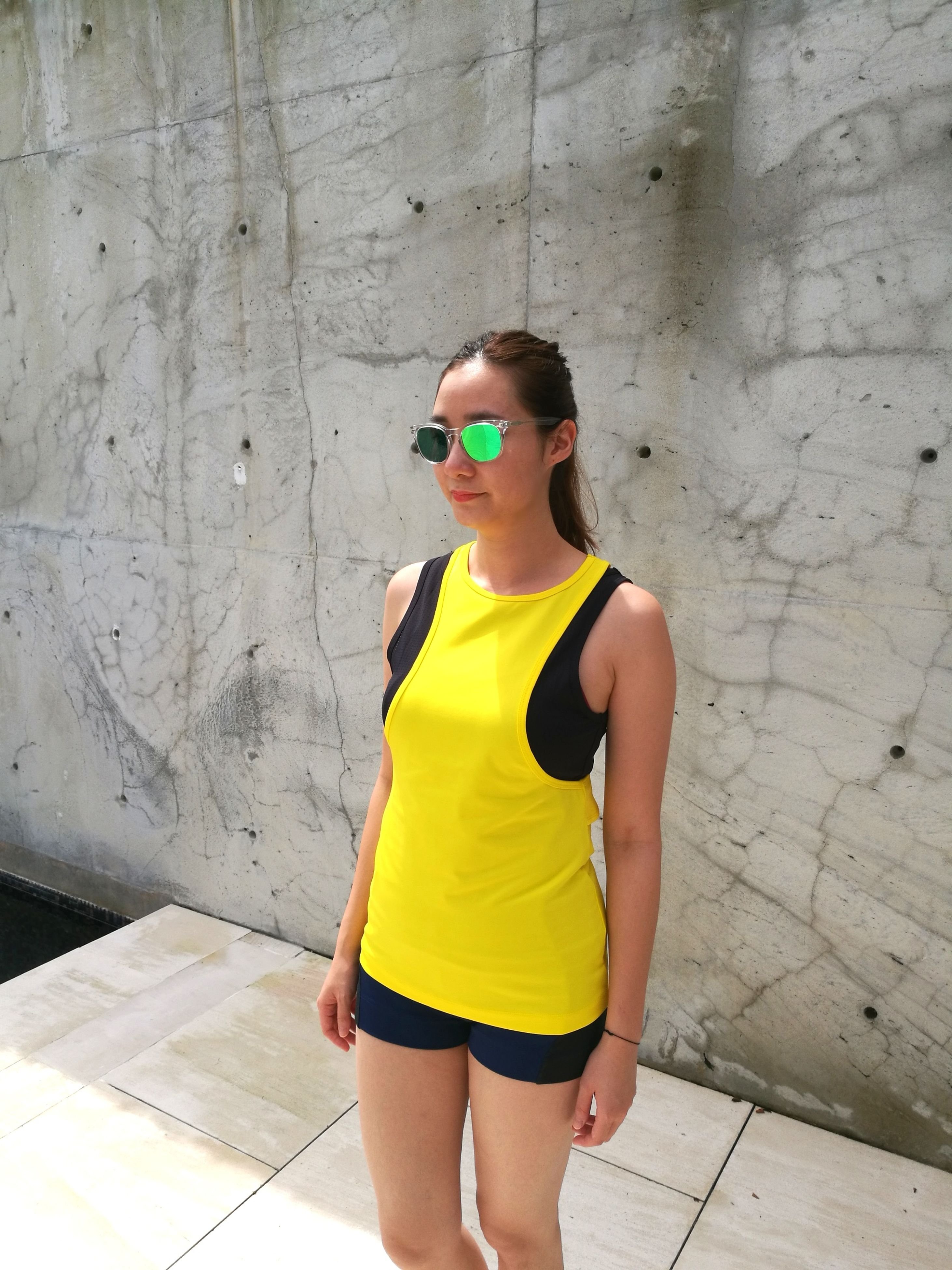 sunglasses, one person, leisure activity, young adult, casual clothing, real people, lifestyles, young women, t-shirt, day, standing, outdoors, yellow, architecture, adult, adults only, people