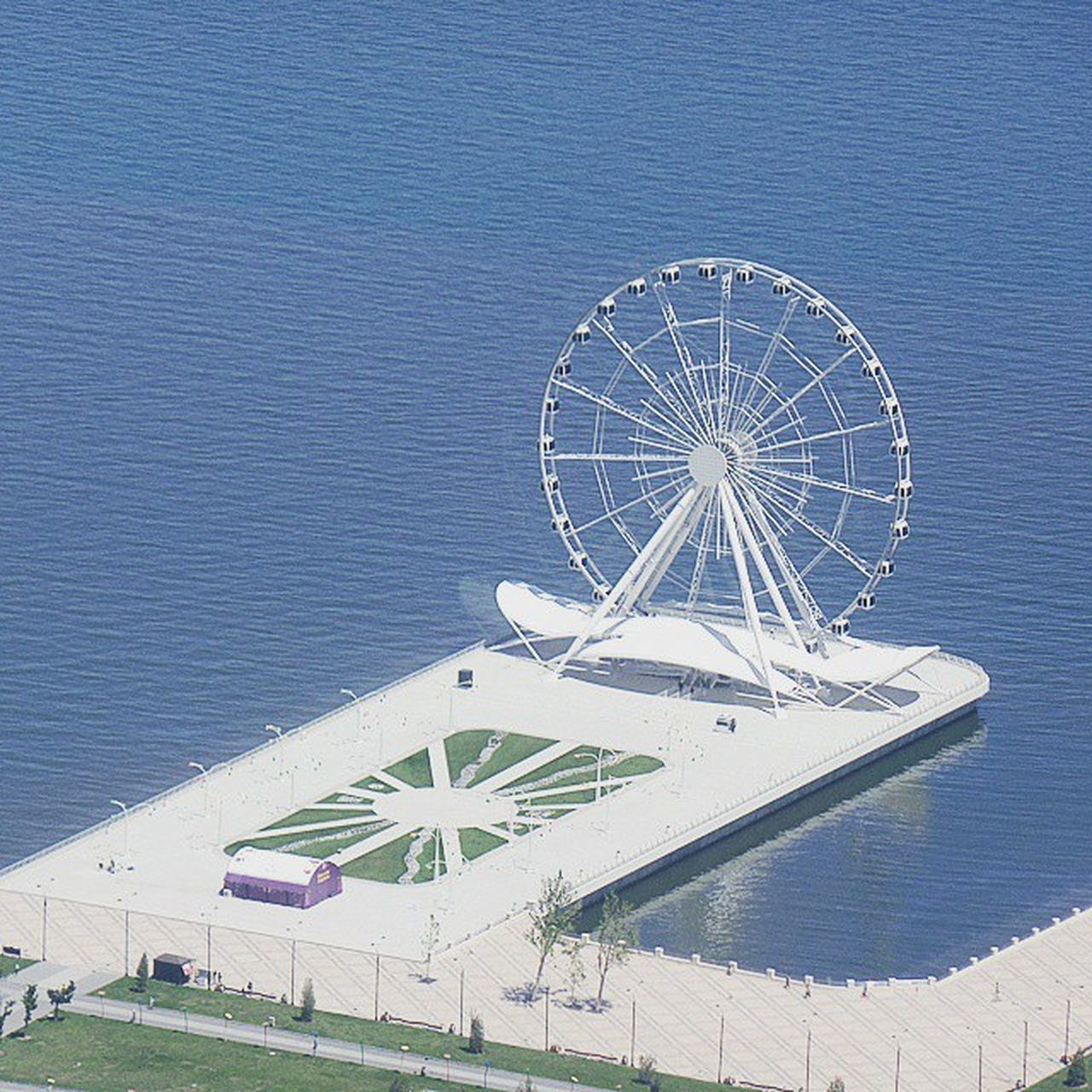 sea, beach, ferris wheel, day, amusement park, nature, outdoors, built structure, water, no people, architecture, building exterior, horizon over water, sky, beauty in nature