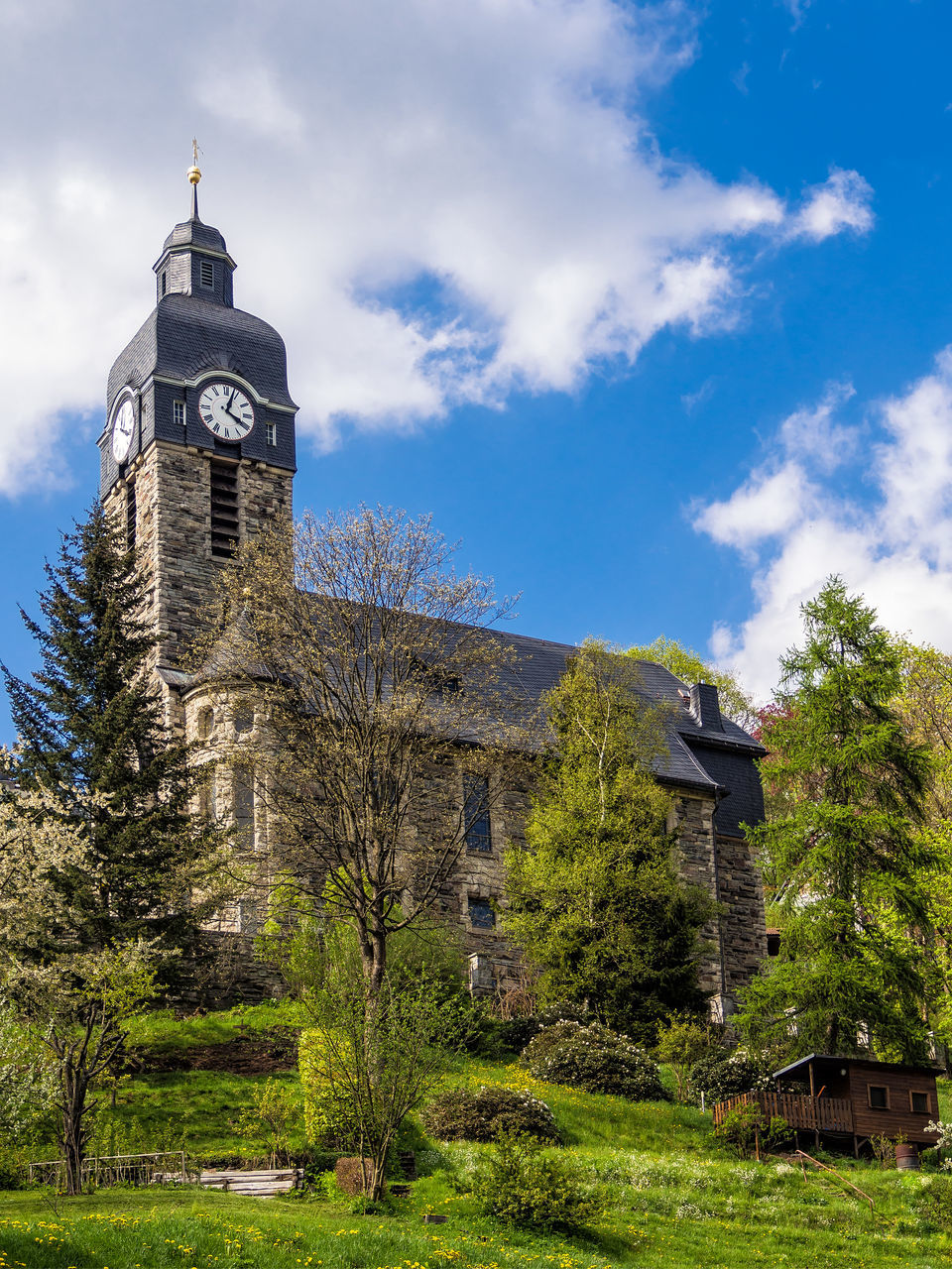 architecture, tree, built structure, building exterior, tower, history, cloud - sky, day, sky, low angle view, clock tower, outdoors, no people, spirituality, religion, place of worship, bell tower, clock, nature, grass