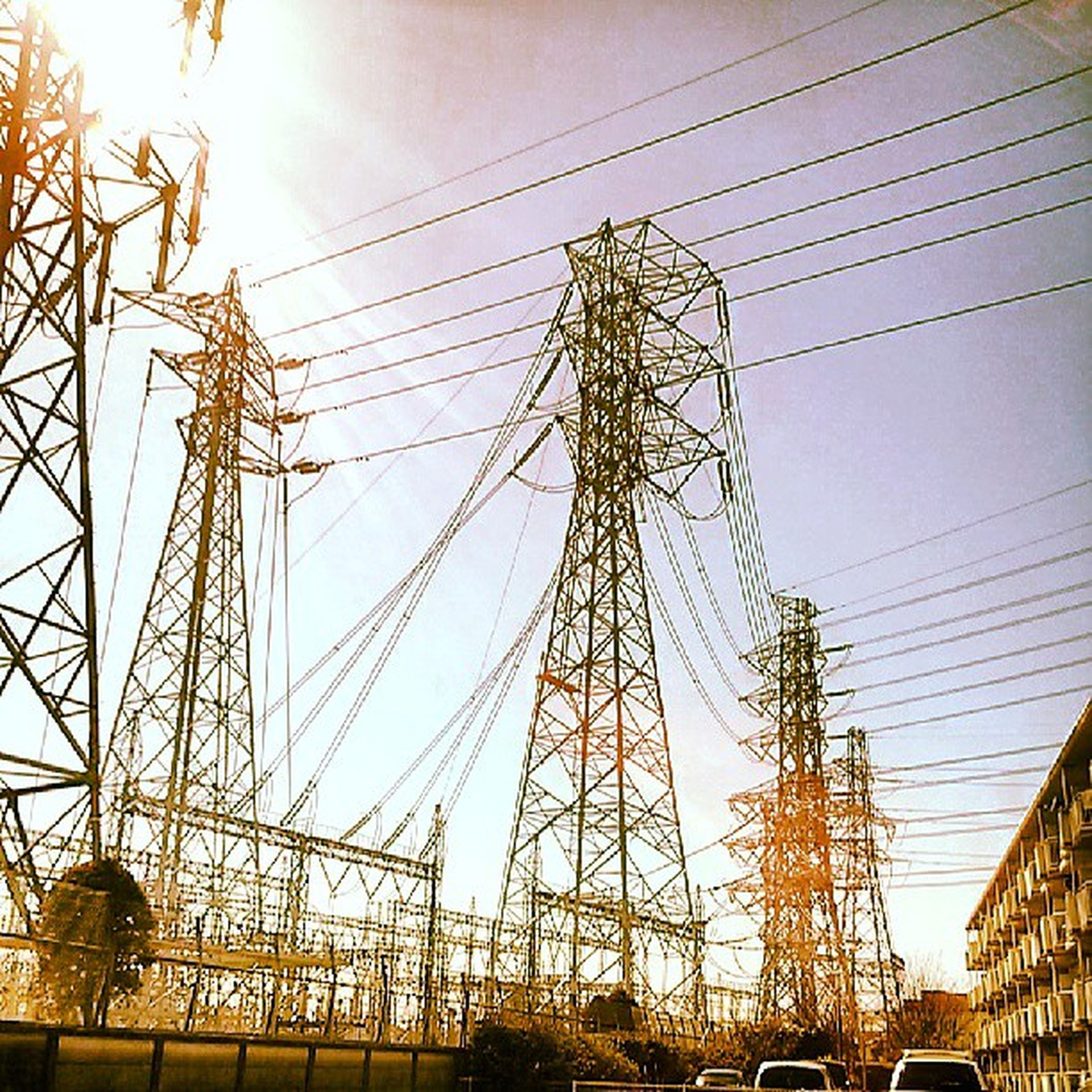 power line, electricity pylon, low angle view, connection, electricity, power supply, cable, built structure, technology, architecture, sky, fuel and power generation, building exterior, clear sky, outdoors, sun, sunlight, complexity, no people, day