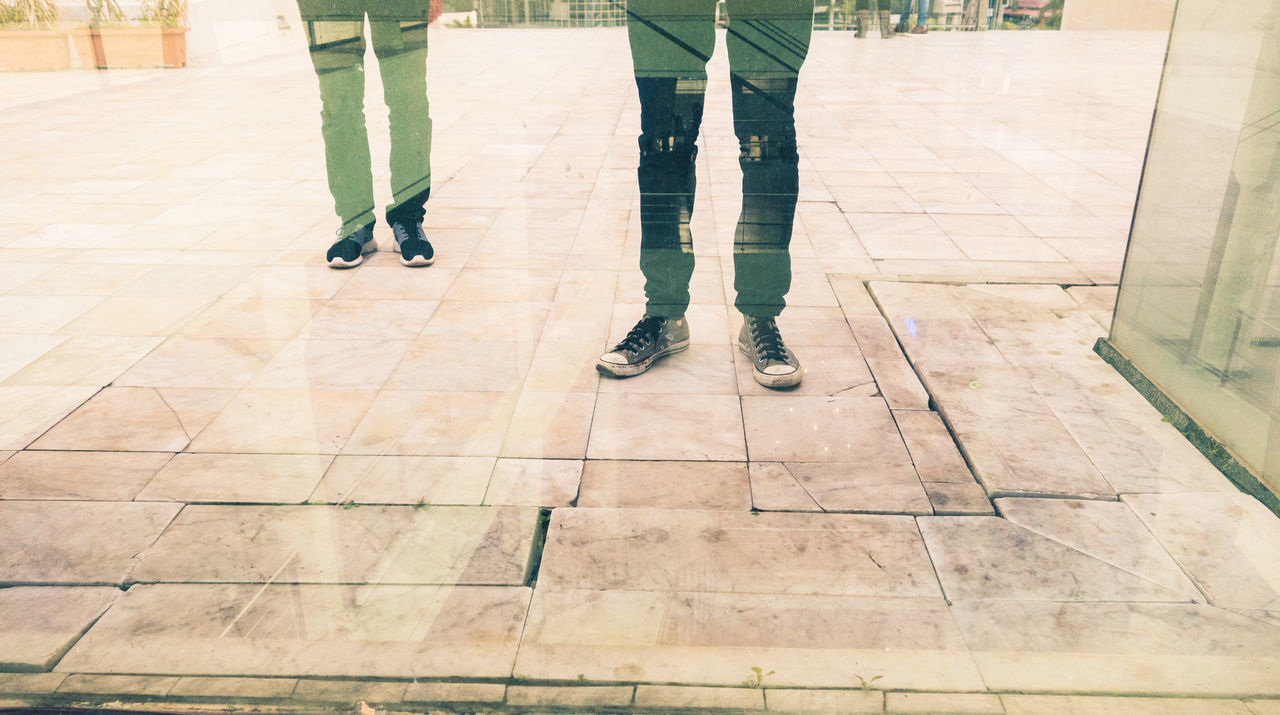 Business City City Life Pants Reflection Concept Conceptual Day Glass Ground Human Body Part Human Leg Indoors  Lifestyles Low Section Men Men Style People people and places Real People Shoes Standing Togetherness Two Two People