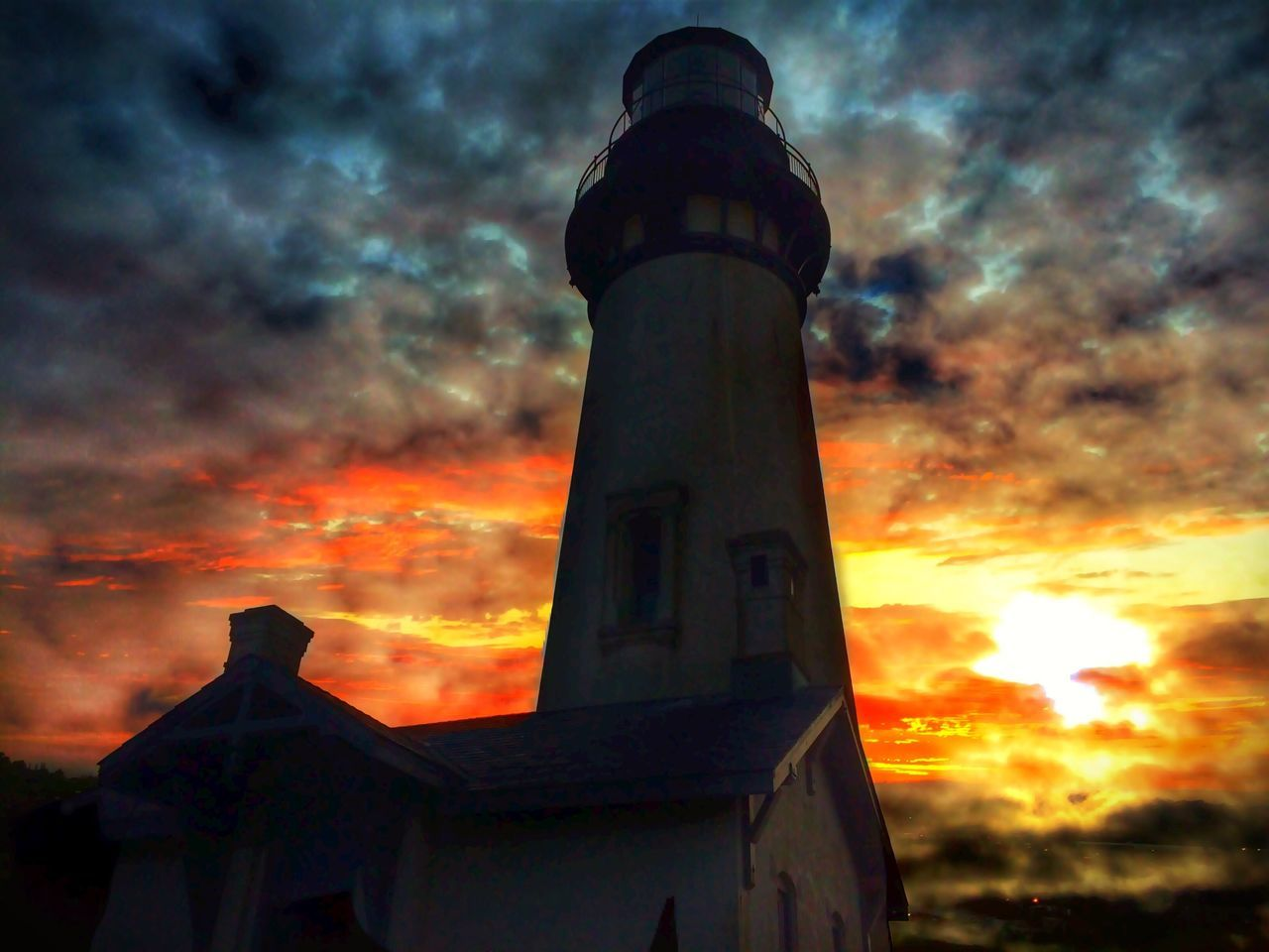 Low Angle View Of Lighthouse Against Cloudy Sky During Sunset