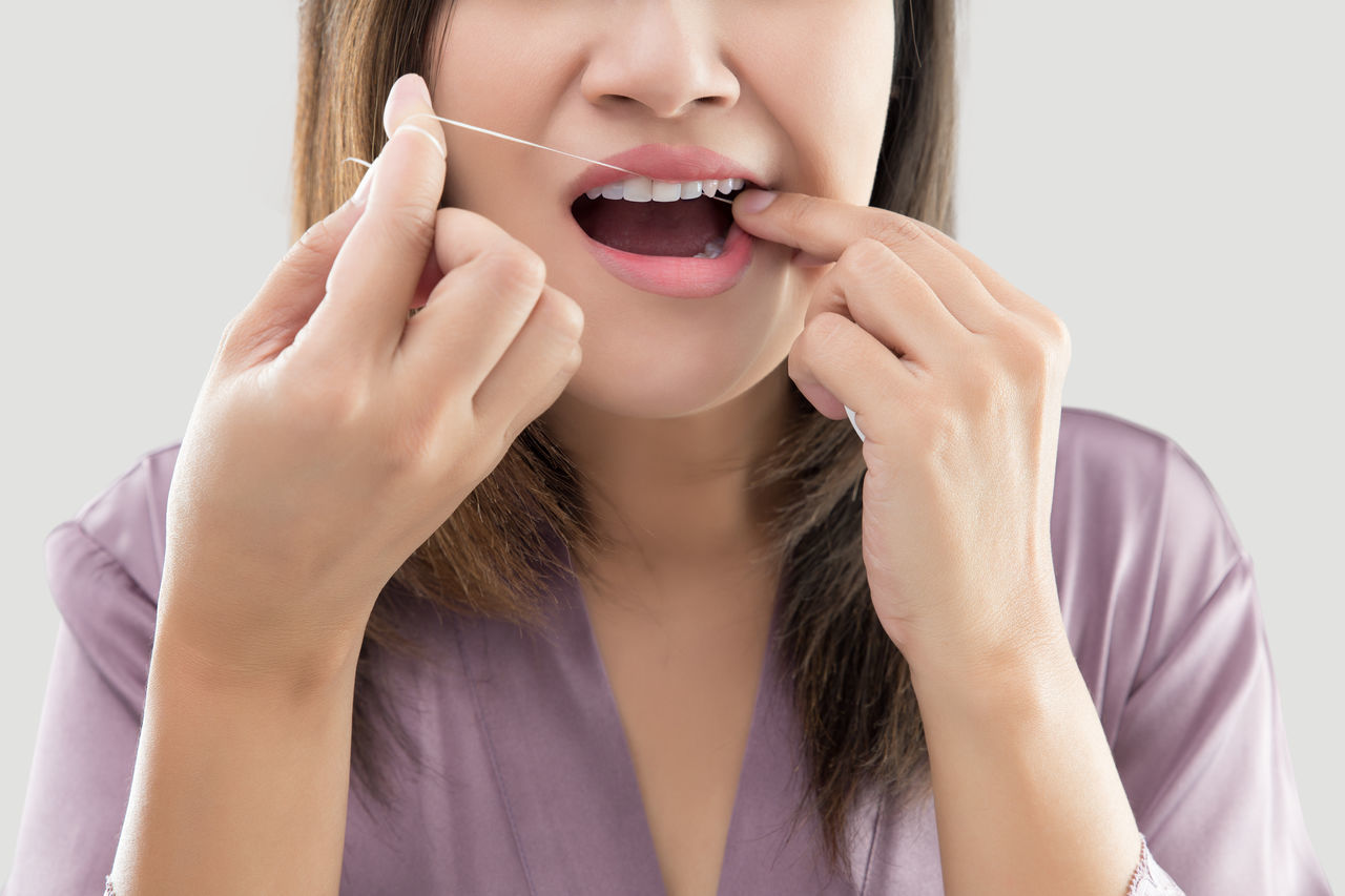 Woman flossing teeth with dental floss ASIA Brushing Cleaning Daily Dental Dentist Dentistry Floss Mouth Woman Clear Close-up Complexion Dental Floss Equipment Flossing Hygienic Oral, Orthodontic Robes Scrub Teeth Tooth Wash Whitening