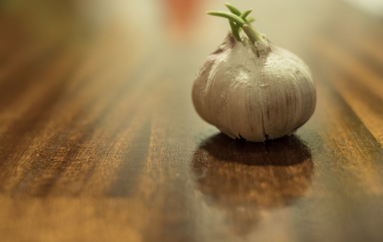 table, food, food and drink, garlic, garlic bulb, selective focus, healthy eating, vegetable, raw food, freshness, no people, indoors, close-up, wood - material, day