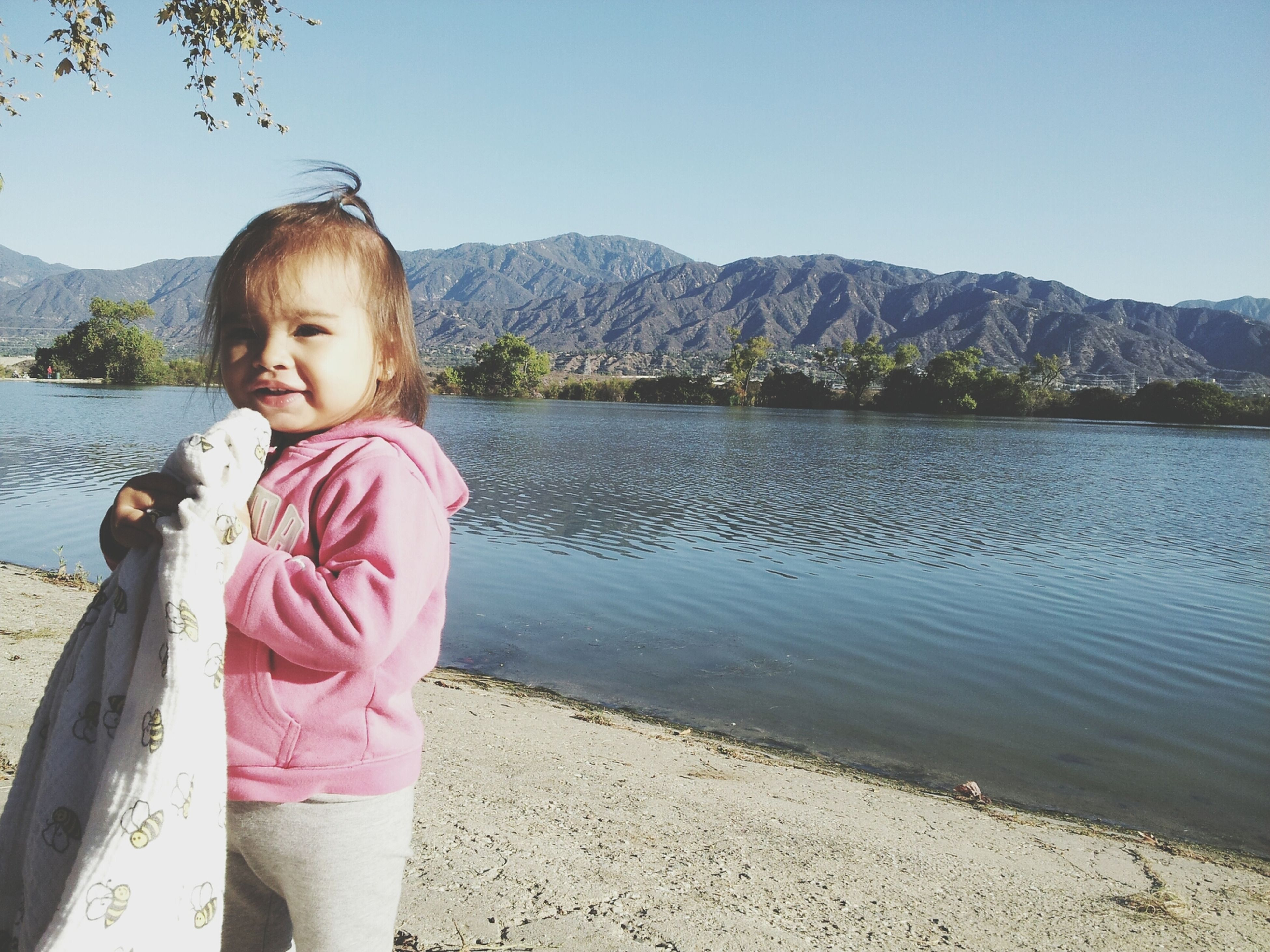 water, lake, lifestyles, casual clothing, leisure activity, standing, person, beauty in nature, nature, tranquility, childhood, scenics, tranquil scene, river, clear sky, mountain, girls, full length
