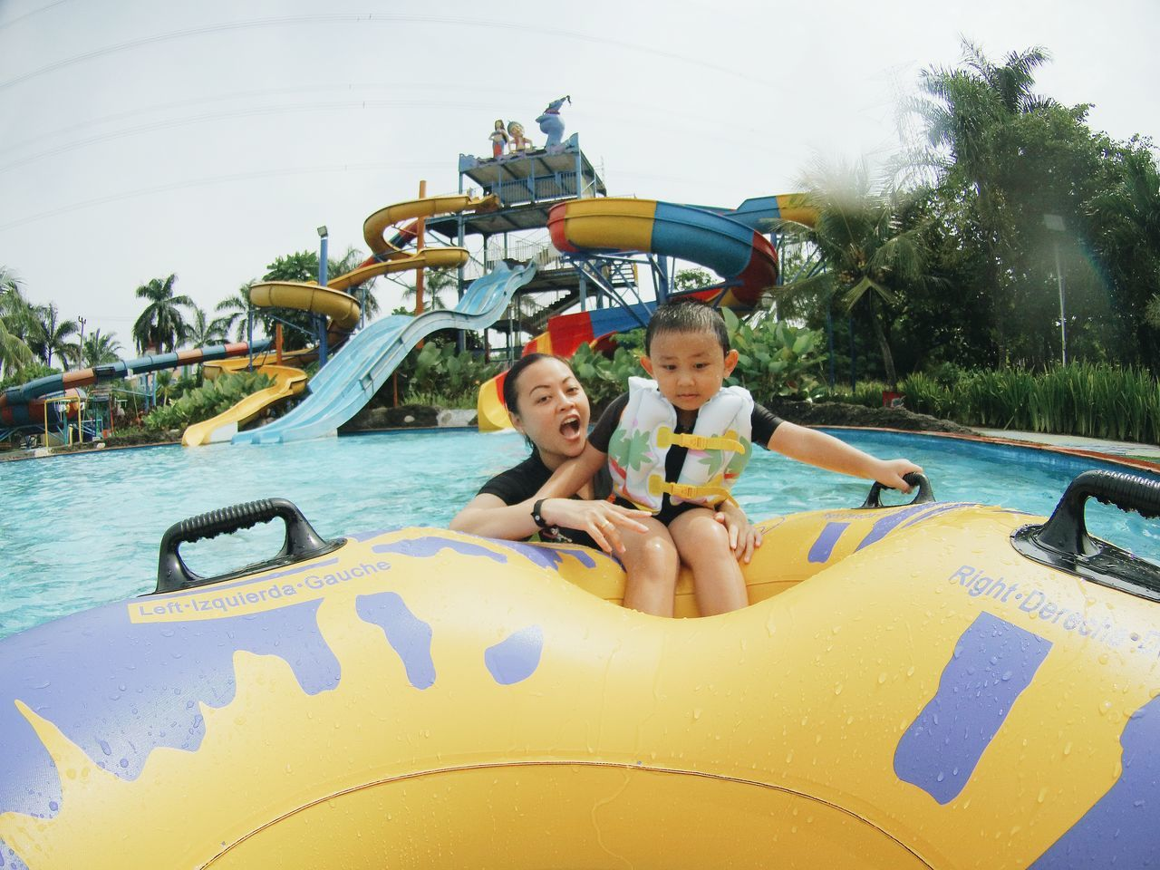 Two People Child Swimming Pool Vacations Fun Togetherness Day Happiness Inflatable  Outdoors Amusement Park People Tree Sky Water Slide Adult Swimming Waterpark Real People