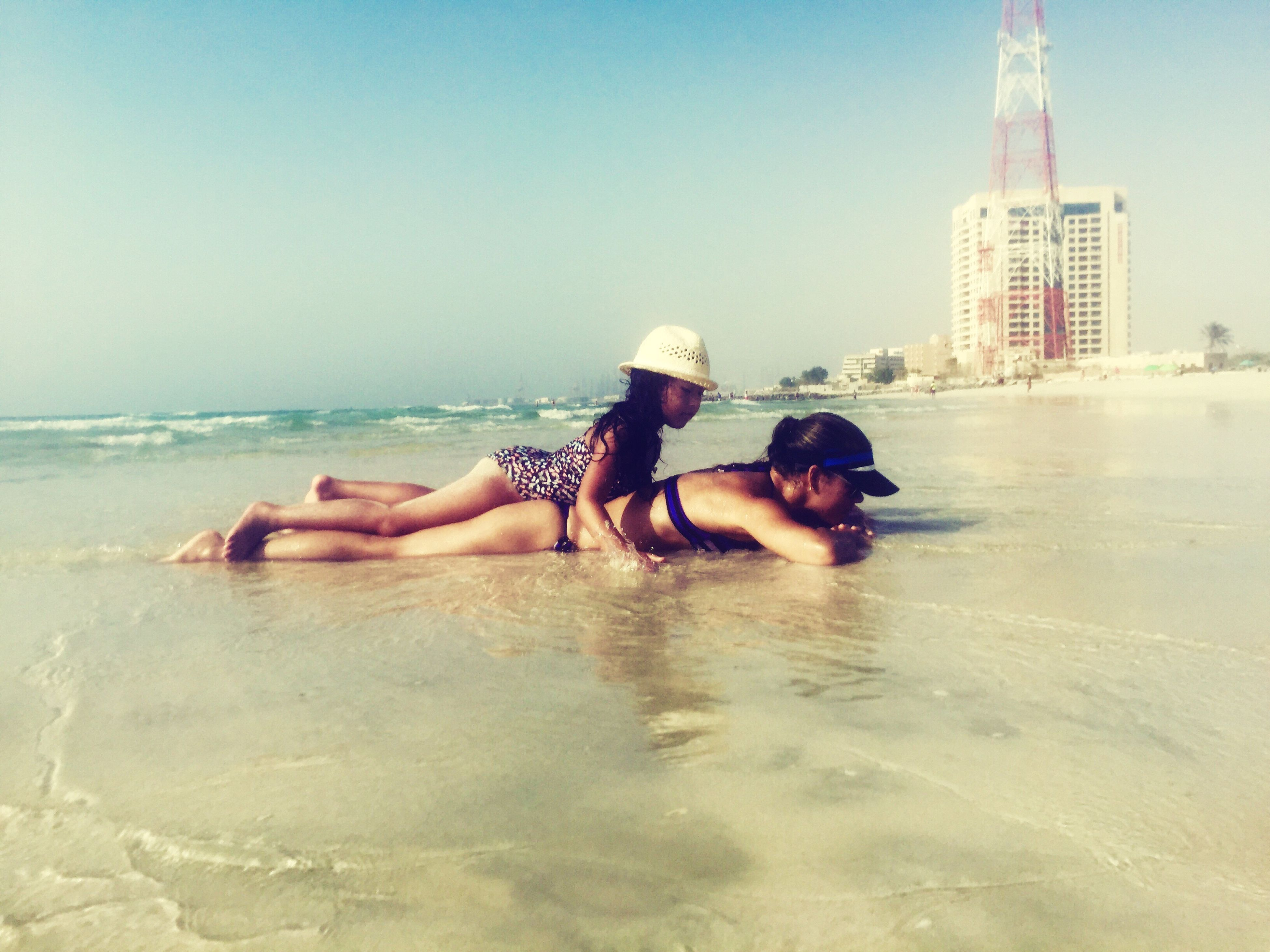 water, sea, real people, leisure activity, two people, young adult, young women, shirtless, vacations, waterfront, lifestyles, building exterior, outdoors, architecture, beach, built structure, day, togetherness, women, sky, men, clear sky, nature, adult, people