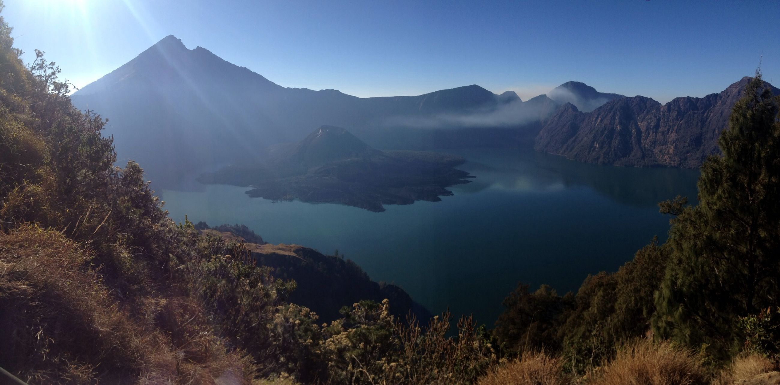 mountain, tranquil scene, tranquility, scenics, beauty in nature, mountain range, water, nature, lake, reflection, sunlight, landscape, idyllic, clear sky, non-urban scene, tree, sky, majestic, physical geography, sun