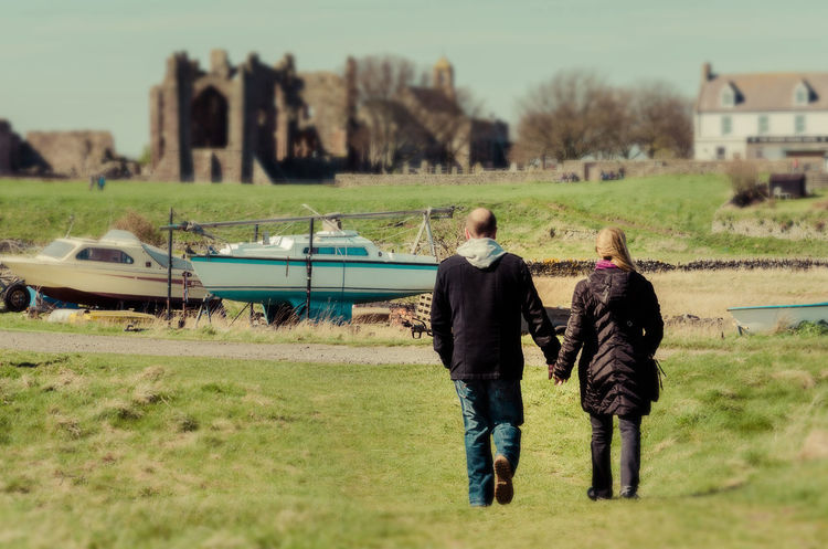 An adult couple walking and sightseeing together in Scotland Couple Hand In Hand Hands Love Married Scotland Travel Traveling Walking Together Walking Around Adults Day Field Grass Holy Island Marriedlife Outdoors People Real People Together Togetherness Travel Destinations Traveling Together Two People Walking