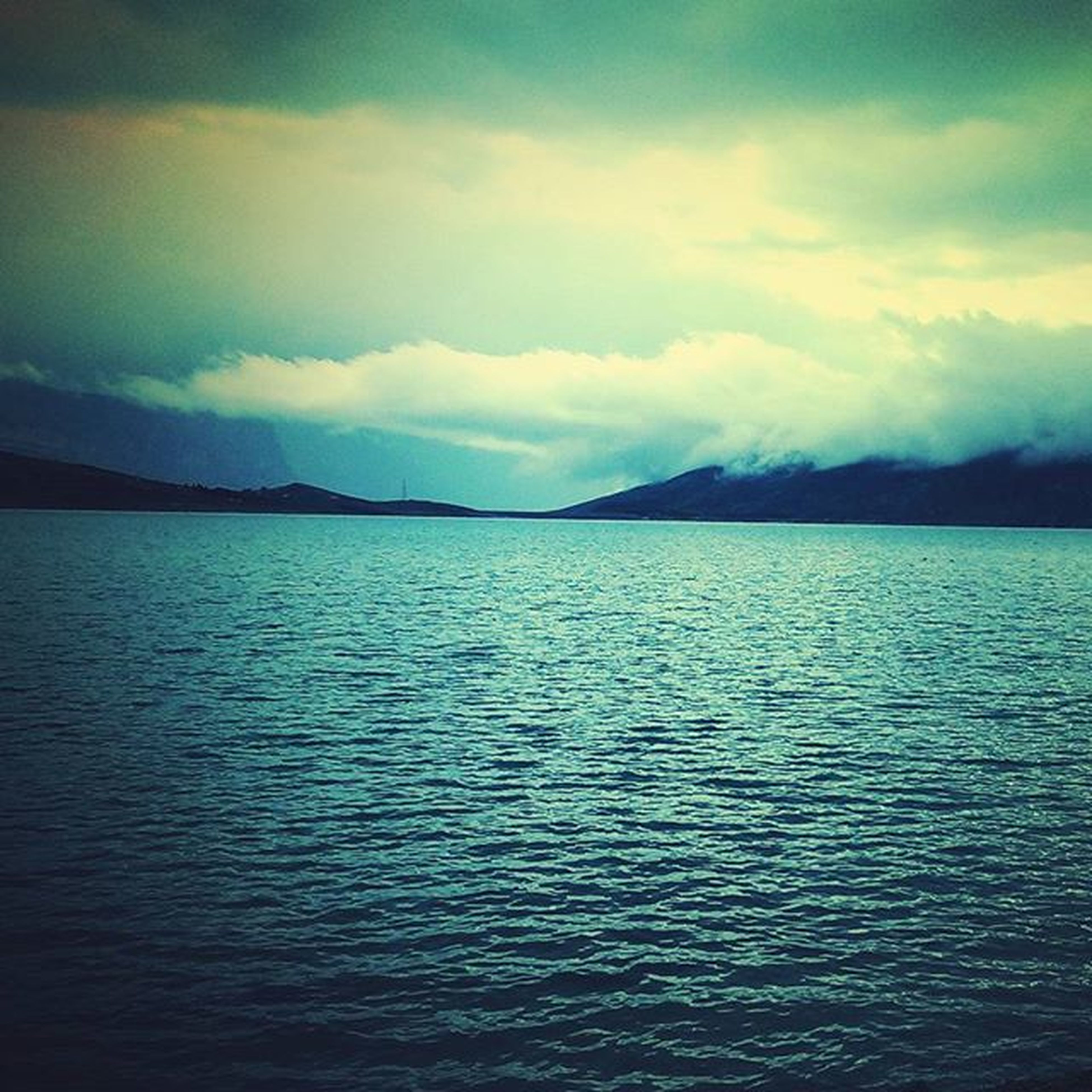 water, tranquil scene, sky, scenics, tranquility, waterfront, beauty in nature, mountain, cloud - sky, nature, cloudy, cloud, sea, lake, mountain range, rippled, idyllic, calm, dusk, outdoors
