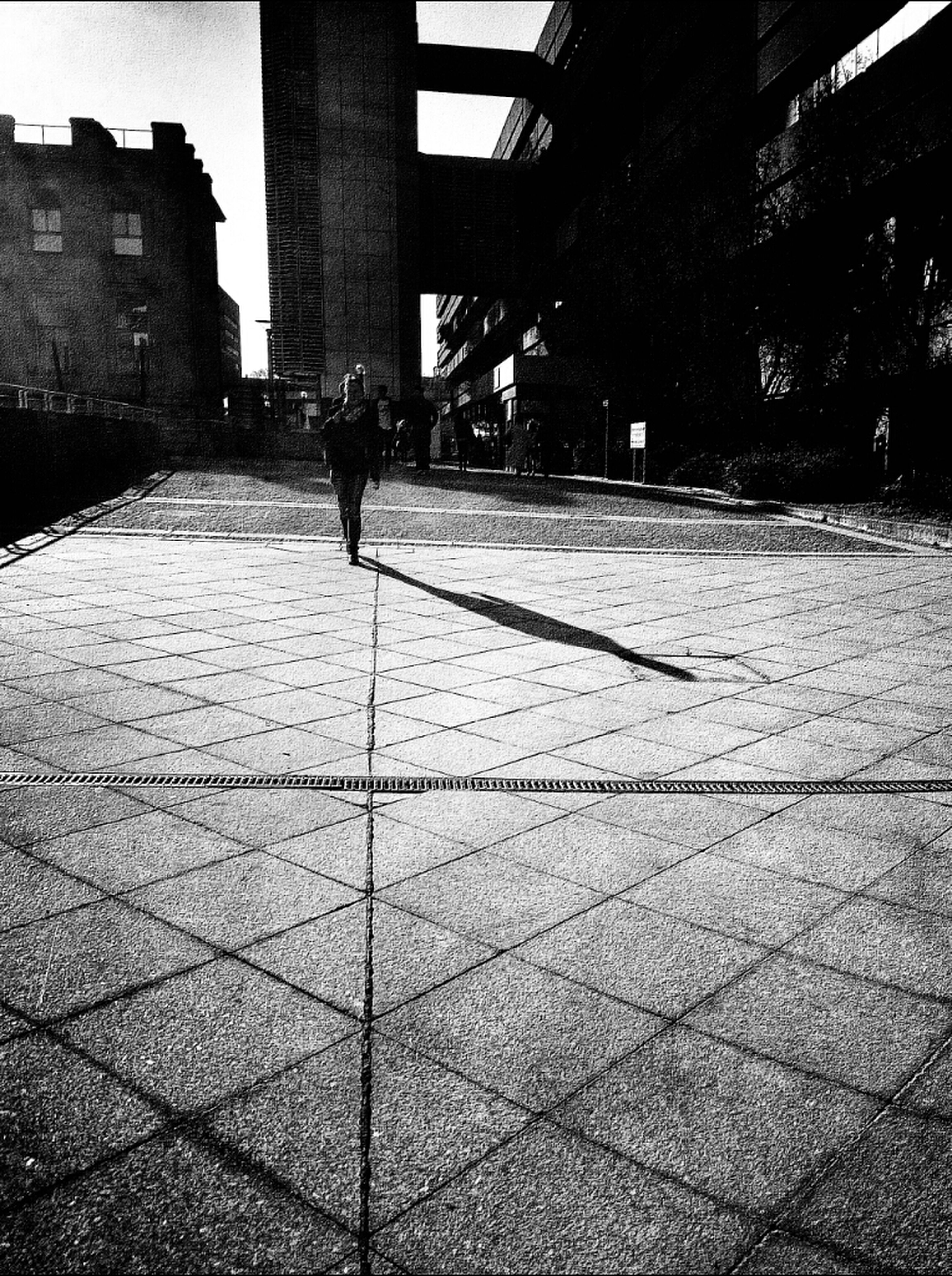 architecture, built structure, building exterior, walking, lifestyles, shadow, cobblestone, men, leisure activity, the way forward, person, sunlight, full length, paving stone, footpath, walkway, street, city
