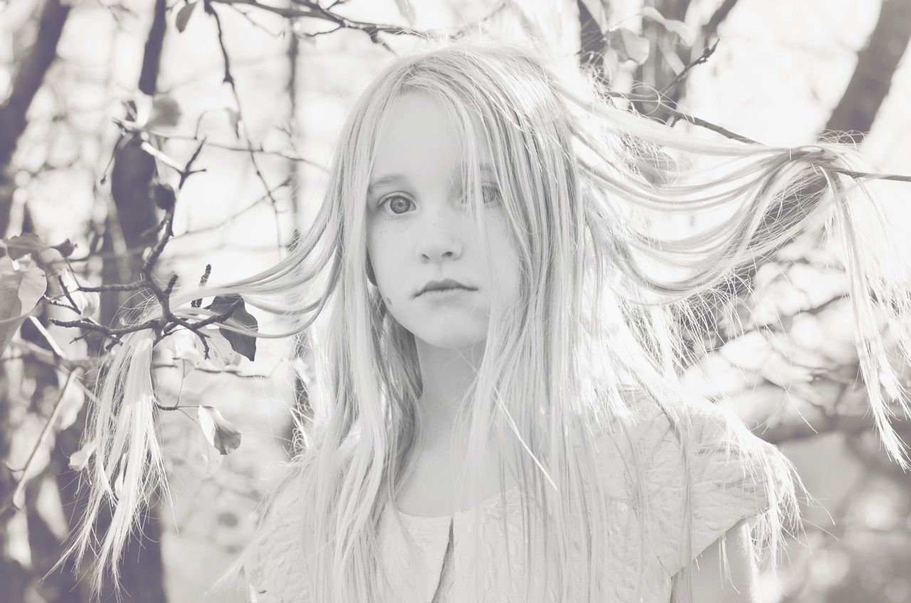Portrait Of Girl With Hair On Twigs In Park