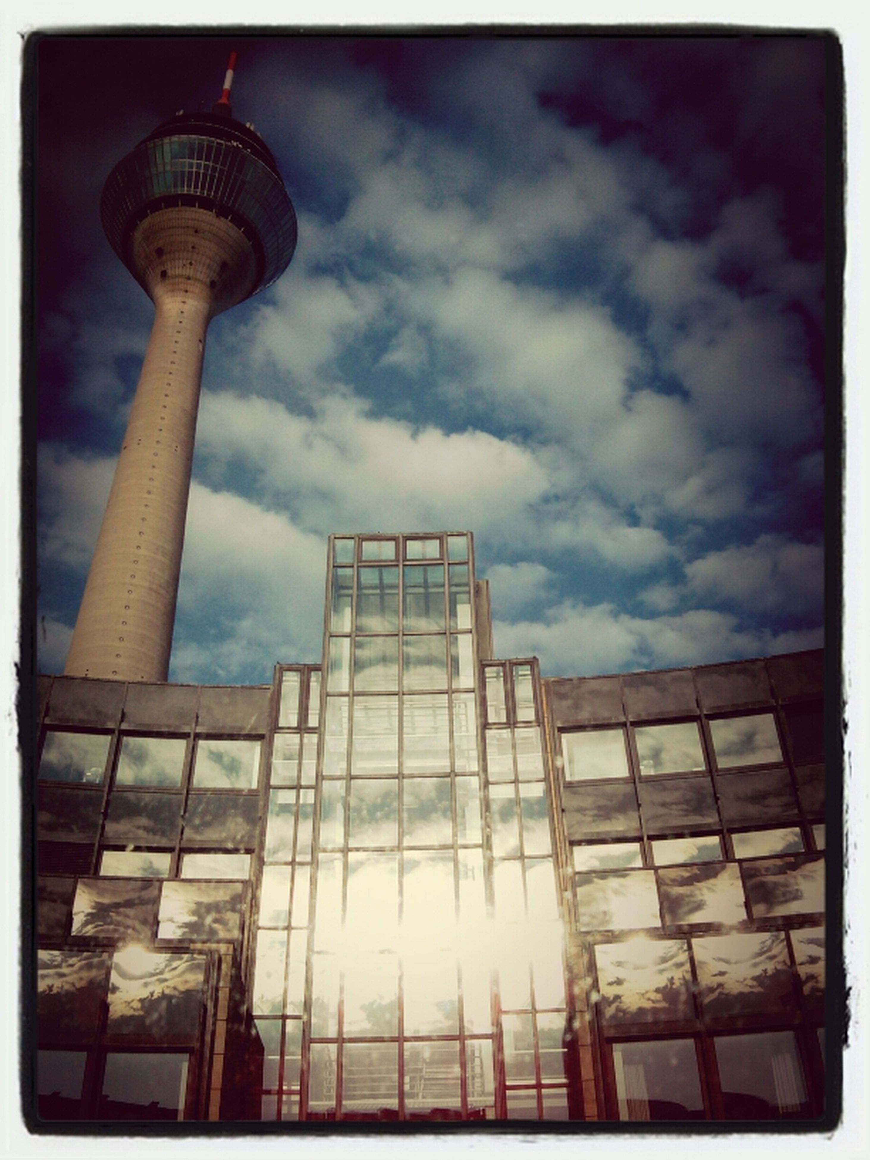 architecture, built structure, building exterior, tower, sky, tall - high, low angle view, transfer print, cloud - sky, city, auto post production filter, famous place, international landmark, travel destinations, capital cities, communications tower, modern, skyscraper, cloudy, communication