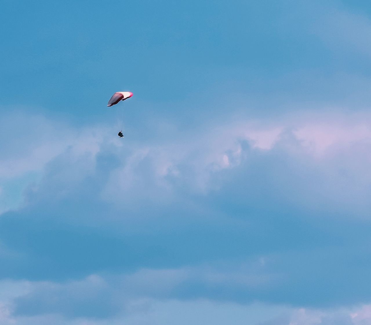 sky, cloud - sky, mid-air, low angle view, parachute, outdoors, nature, adventure, day, beauty in nature, scenics, extreme sports, one person, flying, real people, paragliding