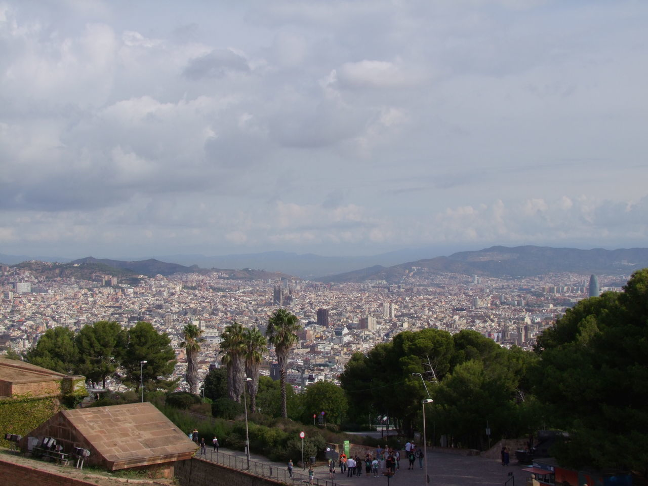 View of Barcelona from Montjuic Castle Barcelona City Cityscape Cloudy Sky Composition Diminishing Perspective Distant View Hazy  High Angle View Montjuic Castle Mountain No People Outdoor Photography Spaın Sunlight And Shade Tourism Tourist Attraction  Tourist Destination Tree Urban Skyline