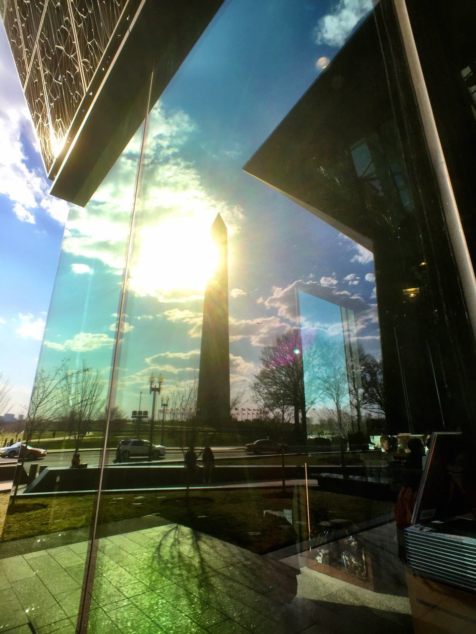 window, sunlight, sunbeam, sky, lens flare, sun, reflection, day, cloud - sky, tree, looking through window, indoors, building exterior, one person, architecture, nature, city, people
