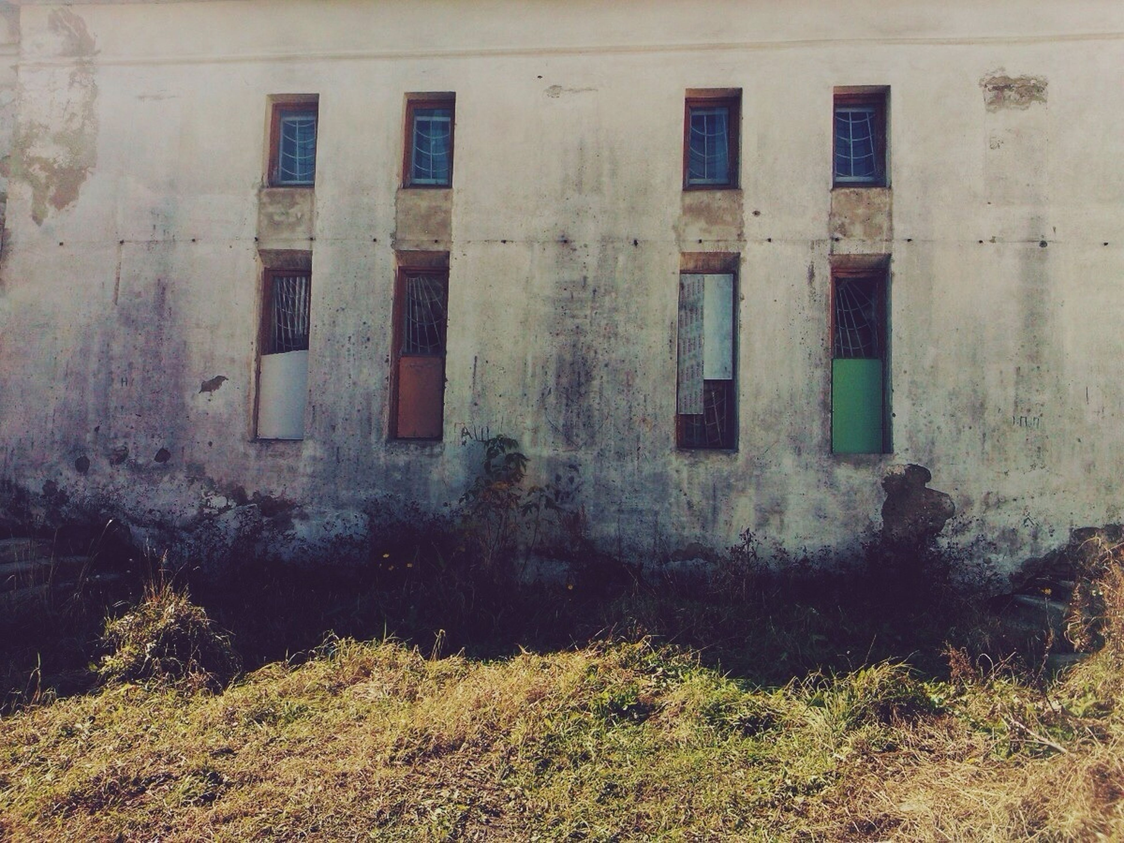 architecture, built structure, building exterior, window, abandoned, damaged, old, obsolete, building, weathered, run-down, deterioration, house, grass, wall - building feature, bad condition, day, outdoors, residential structure, residential building